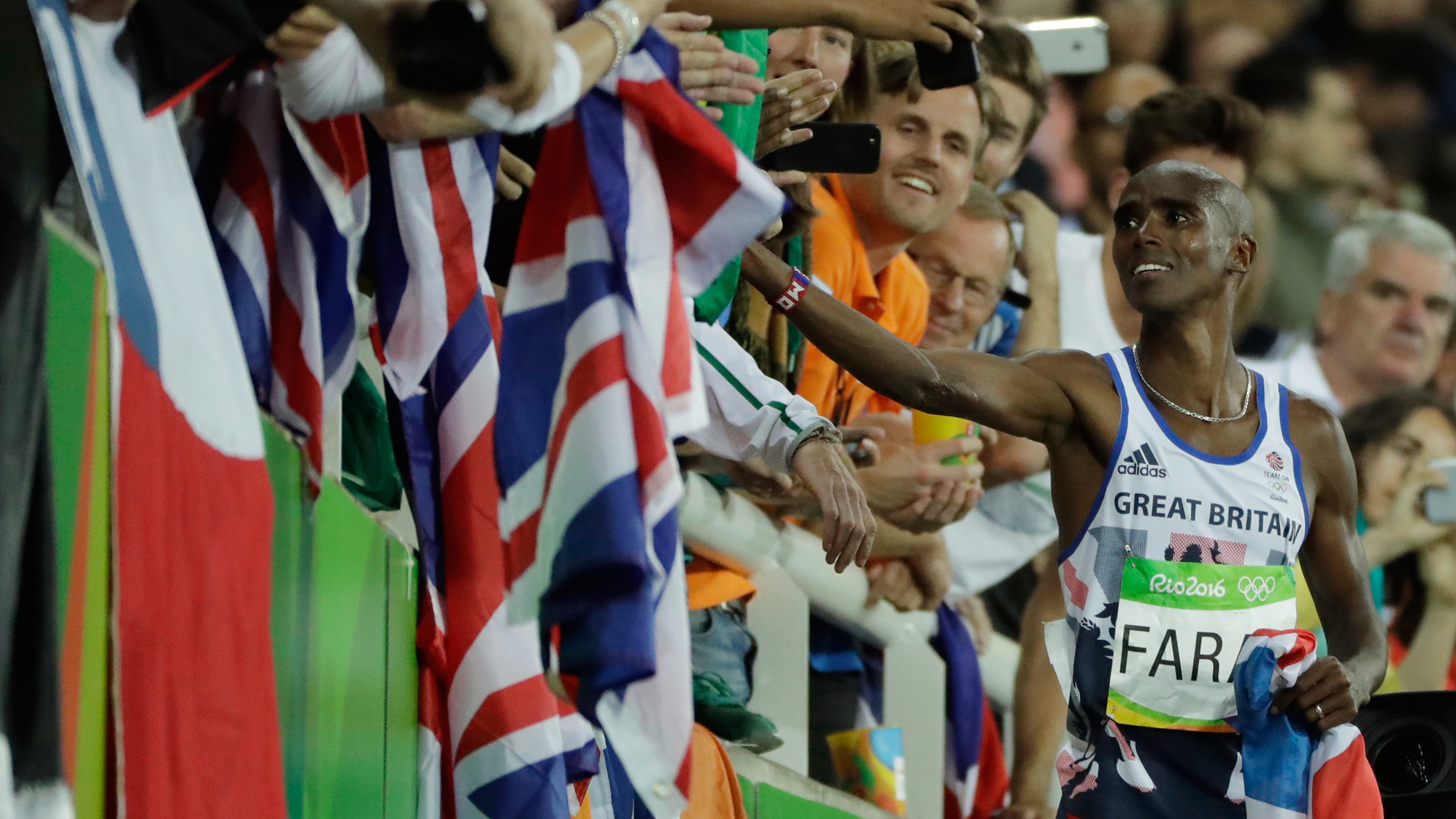 Britain's Mo Farah greets spectators after winning the gold medal in the men's 10,000-meter final during the athletics competitions of the 2016 Summer Olympics at the Olympic stadium in Rio de Janeiro, Brazil, Saturday, Aug. 13, 2016. (AP Photo/Jae C. Hong)
