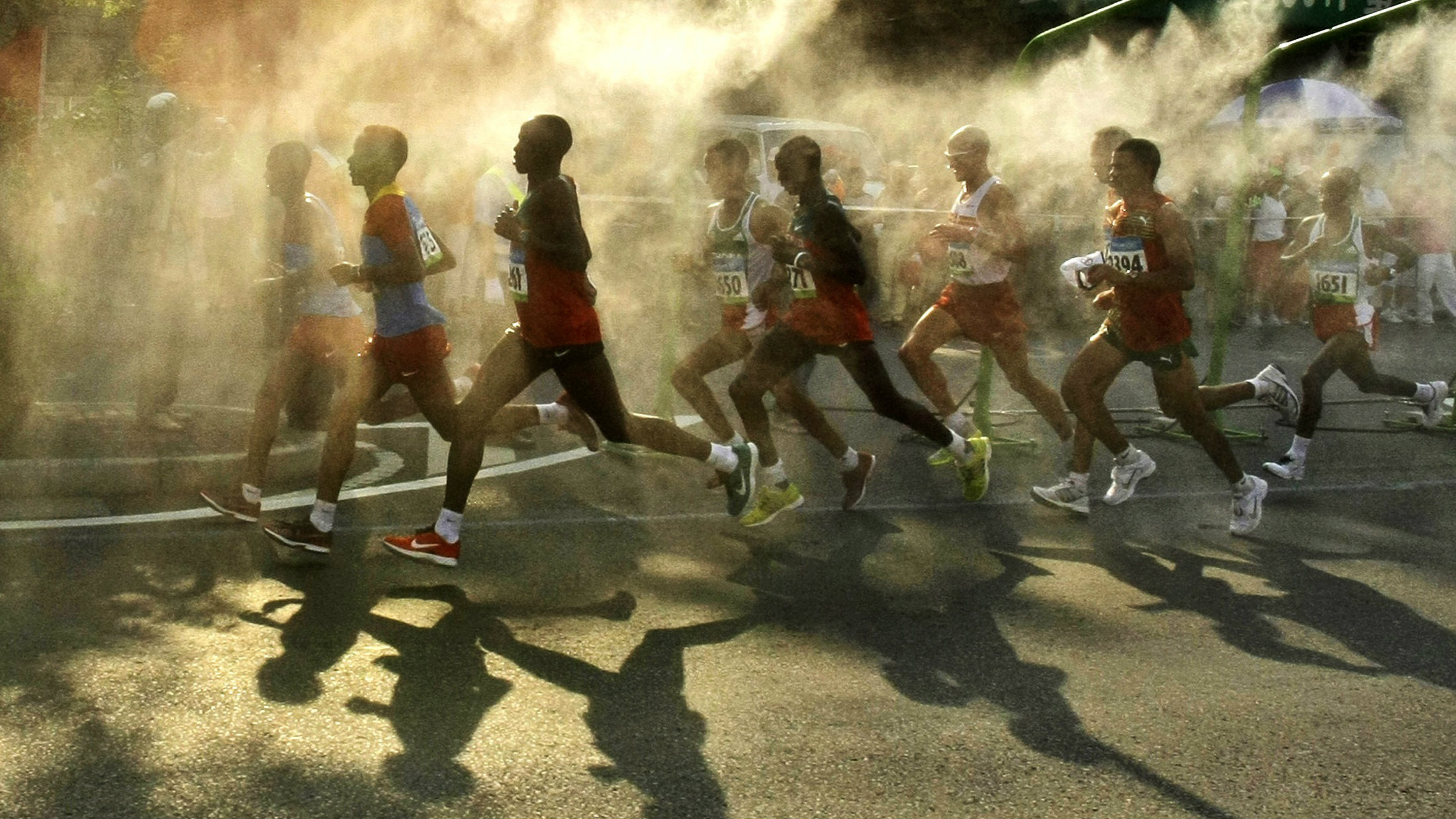 Athletes cast shadows as they run under cooling mist in the men's marathon during the Beijing 2008 Olympic Games.