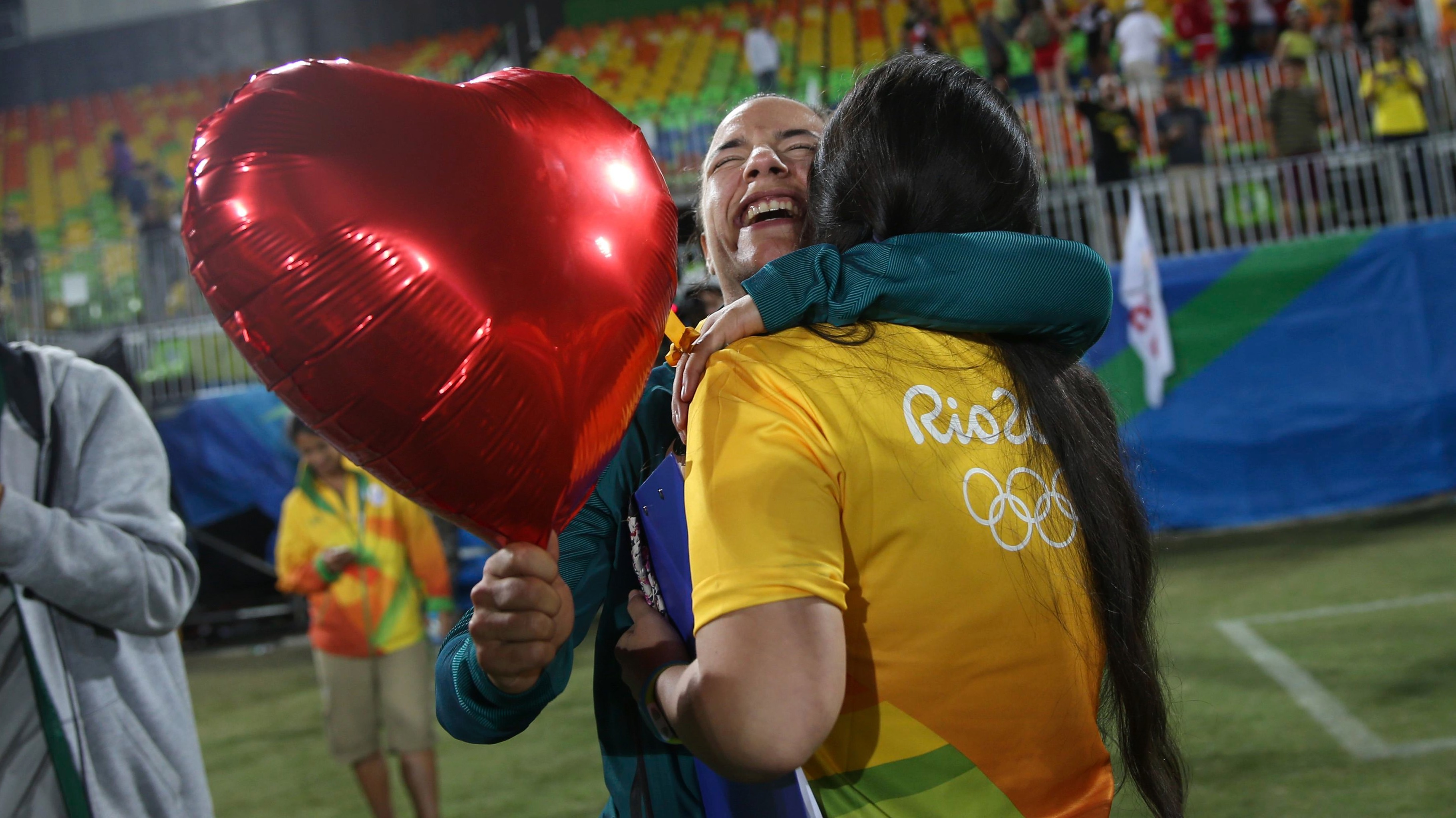 2016 Rio Olympics - Rugby - Women's Gold Medal Match Australia v New Zealand - Deodoro Stadium - Rio de Janeiro, Brazil - 08/08/2016.  Rugby player Isadora Cerullo (BRA) of Brazil hugs Marjorie, a volunteer, after receiving her wedding proposal on the sidelines of the women's rugby medal ceremony. REUTERS/Alessandro Bianchi (BRAZIL  - Tags: SPORT OLYMPICS SPORT RUGBY) FOR EDITORIAL USE ONLY. NOT FOR SALE FOR MARKETING OR ADVERTISING CAMPAIGNS.   - RTSLYLE