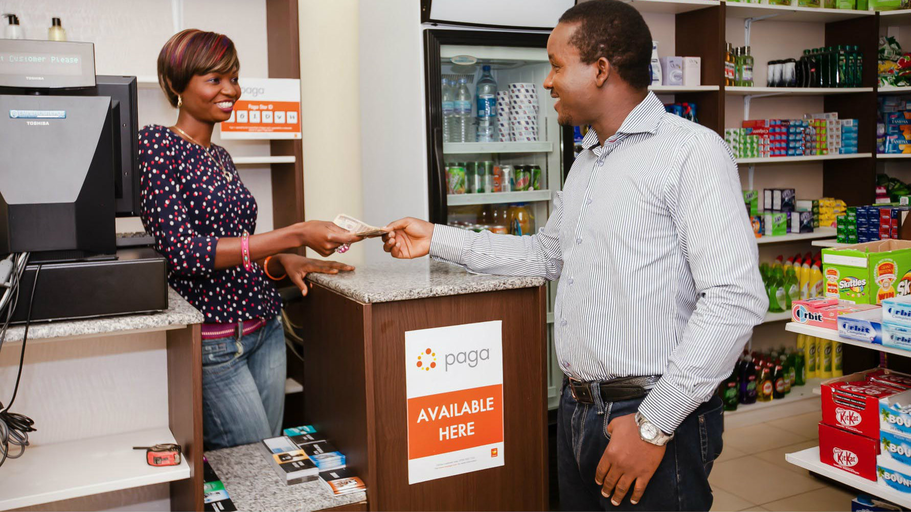 A Paga agent carrying a transaction at a local shop