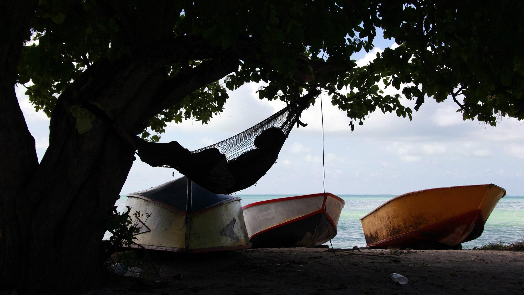 A man sleeps in a hammock next to fishing boats in the town of Bairki on South Tarawa in the central Pacific island nation of Kiribati May 23, 2013. REUTERS/David Gray (KIRIBATI - Tags: ENVIRONMENT SOCIETY POLITICS)