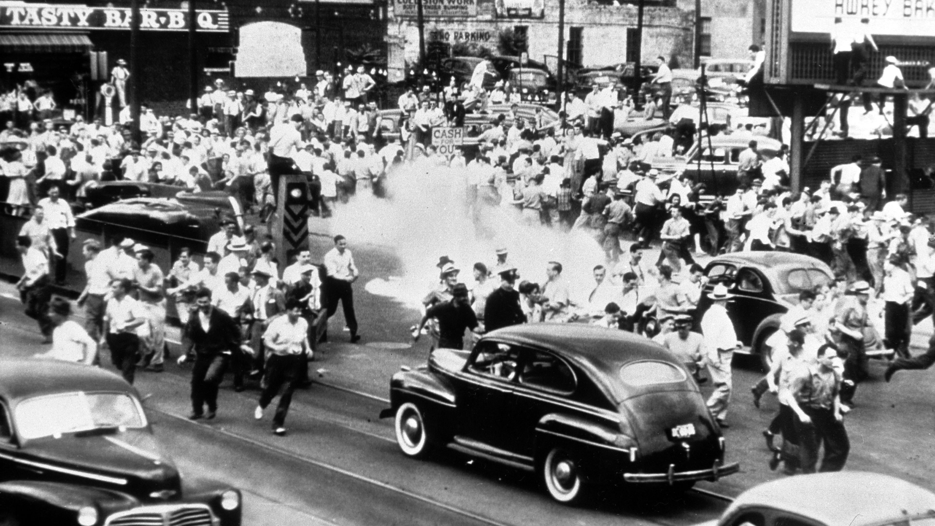 Police use tear gas to disperse a crowd gathered on the main street of Detroit, Michigan, in an effort to halt race rioting, June 21, 1943. Some people were killed and hundreds were injured in the riots. (AP Photo)