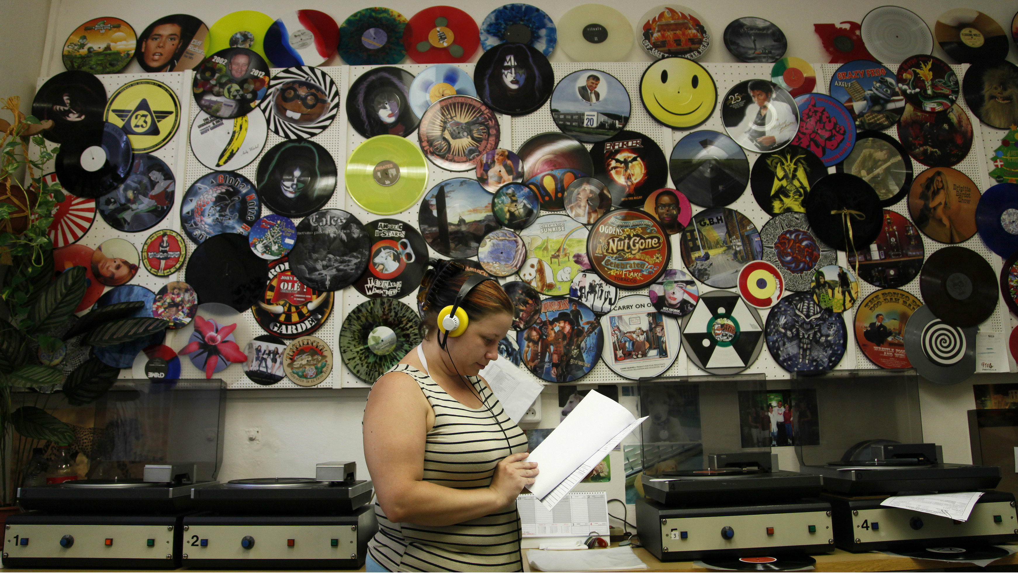 A woman listening to records in a record store.