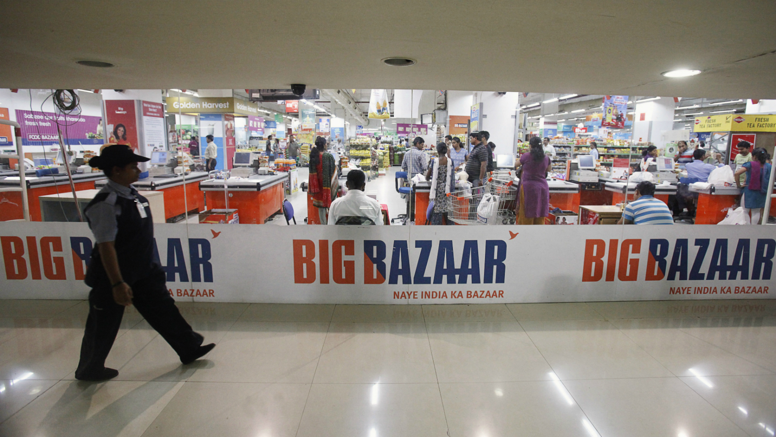 A security personnel walks past the Big Bazaar retail store in Mumbai June 9, 2012. Six months after the government backtracked on plans to allow foreign retail giants such as Wal-Mart Stores and Carrefour to form joint ventures, cash-starved domestic chains are selling assets, shutting stores, and scaling back expansion plans.