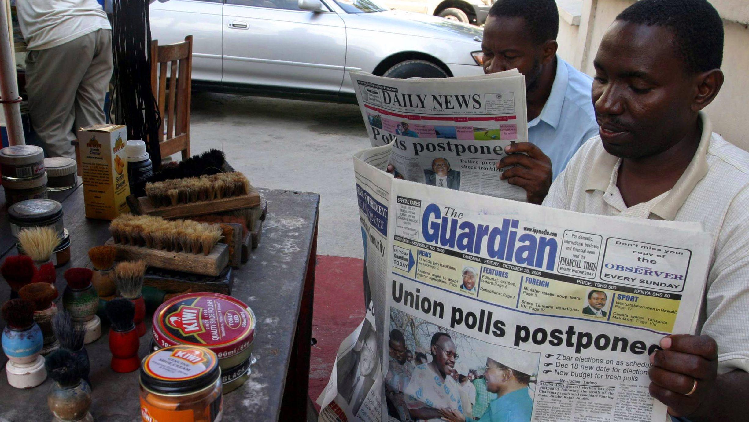 Tanzanian shoe shiners read newspapers in Dar es Salaam