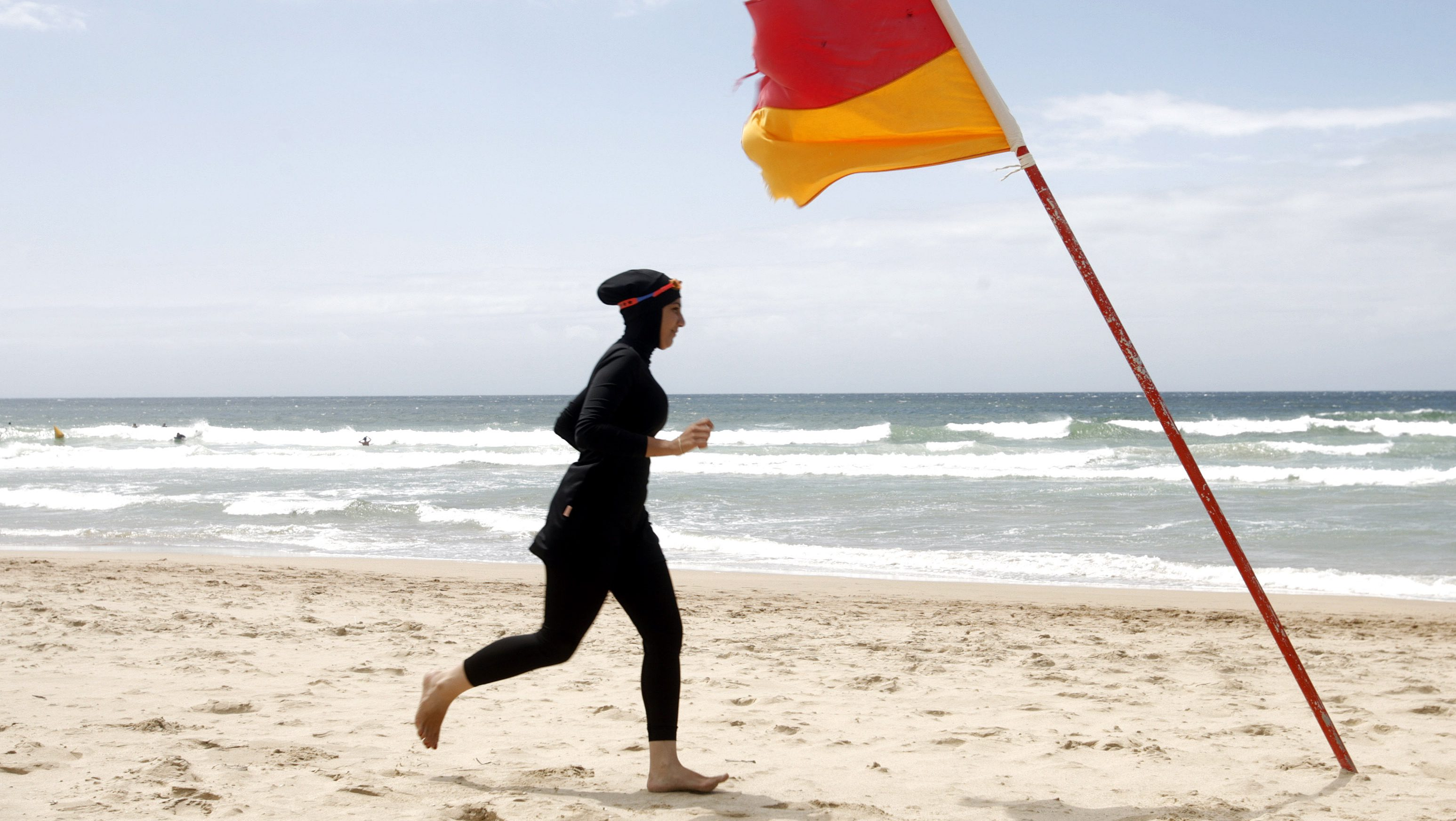 """Twenty-year-old trainee volunteer surf life saver Mecca Laalaa runs along North Cronulla Beach in Sydney during her Bronze medallion competency test January 13, 2007. Specifically designed for Muslim women, Laalaa's body-covering swimming costume has been named the """"burkini"""" by its Sydney based designer Aheda Zanetti.   REUTERS/Tim Wimborne (AUSTRALIA) - RTR1L4WG"""