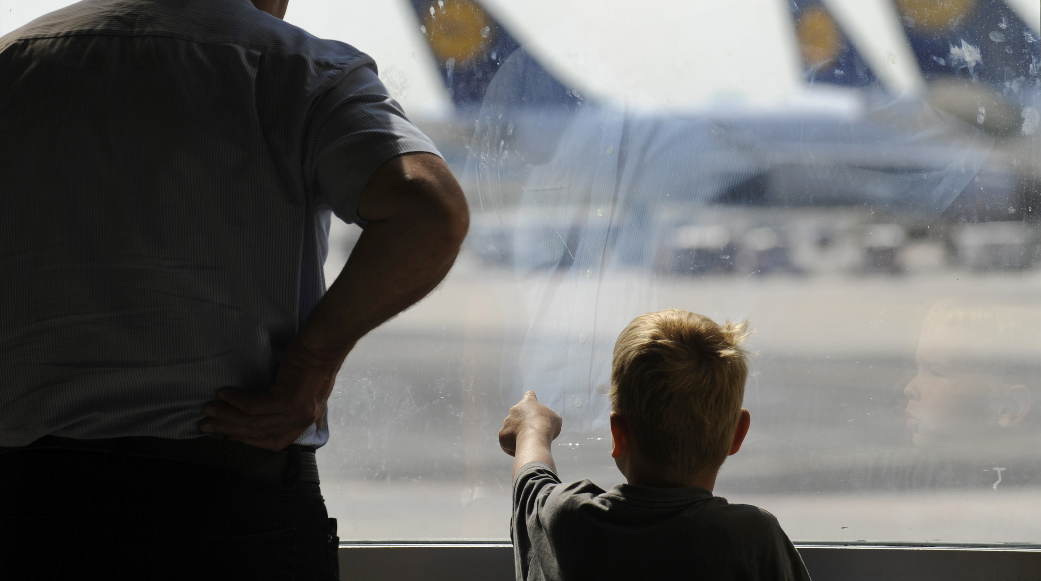 Child points near airplanes of German airline Lufthansa that are parked at Frankfurt airport