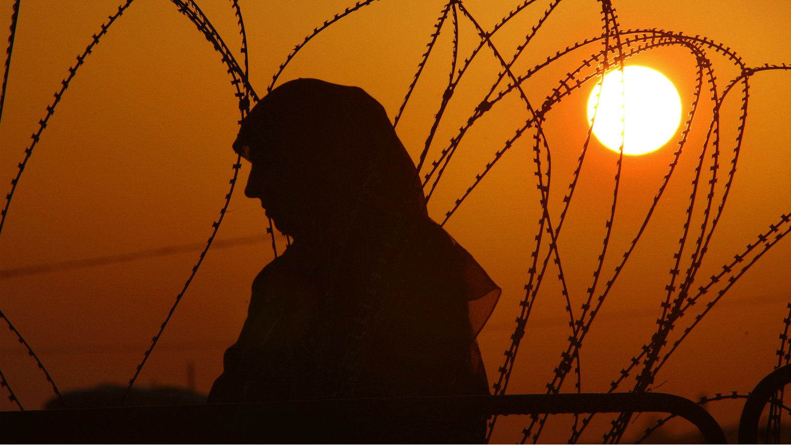 A Palestinian woman waits behind barbed wire for permission to cross Qalandiya checkpoint near the West Bank city of Ramallah early September 18, 2009, as she tries to reach the al-Aqsa mosque in Jerusalem on the fourth and last Friday of the Muslim holy month of Ramadan. Muslims around the world abstain from eating, drinking and sexual relations from sunrise to sunset during Ramadan, the holiest month in the Islamic calendar.