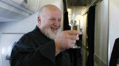 Renowned chef Michel Richard toasts with a glass of champagne as OpenSkies cabin crew Sabine Pena looks on aboard one of Openskies' Boeing 757-200 jets