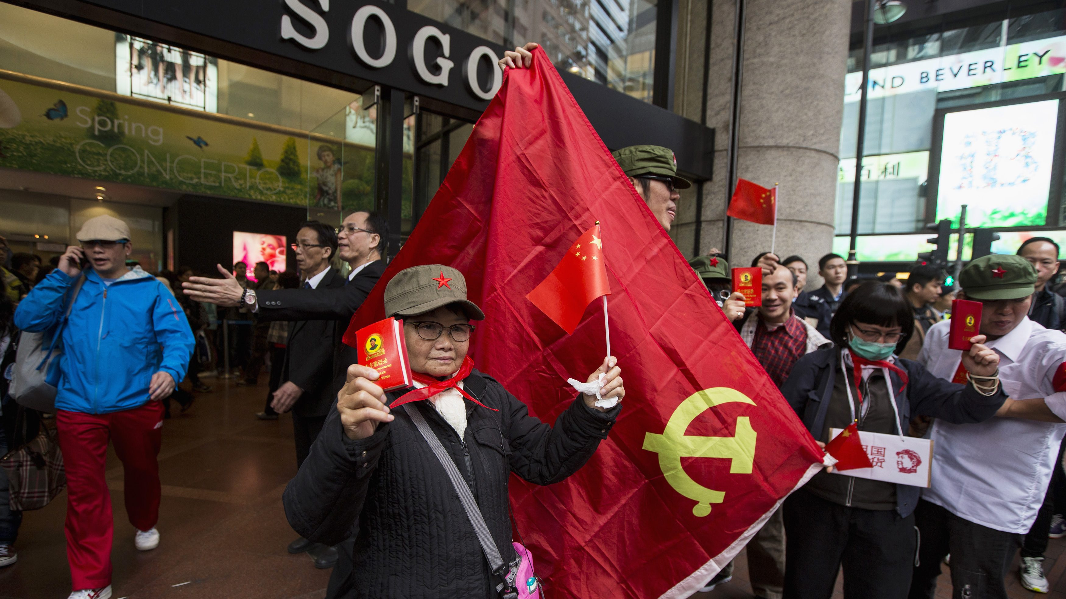 """Protester hold a """"Quotations from Chairman Mao Tse-tung"""" book, commonly known as the """"Little Red Book"""", and Communist Party of China flag during an anti-mainland tourist rally outside a shopping mall in Hong Kong's famous Causeway Bay shopping district March 16, 2014. Hundreds of protesters joined a rally organized by an anti-mainland group in Causeway Bay, mocking and dissuading mainland Chinese shoppers from buying imported daily essentials in Hong Kong. The protesters claim that prices of imported daily essentials have gone up and supply is limited, according to local media. REUTERS/Tyrone Siu (CHINA - Tags: POLITICS BUSINESS CIVIL UNREST TRAVEL) - RTR3H9RF"""