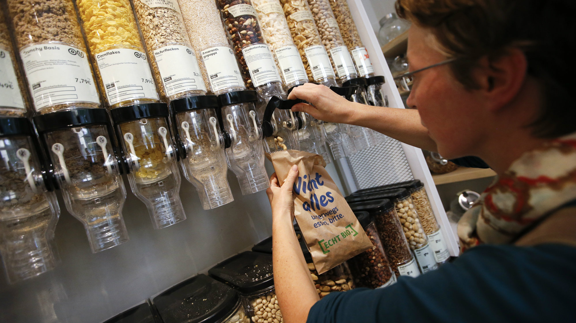 A customer fills up a bag with nuts at a grocery store in Berlin.
