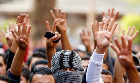 Cairo University students shout slogans against the government and flash the 'V' and Rabaa signs after the verdict of former Egyptian President Hosni Mubarak's trial, at the university's campus in Giza