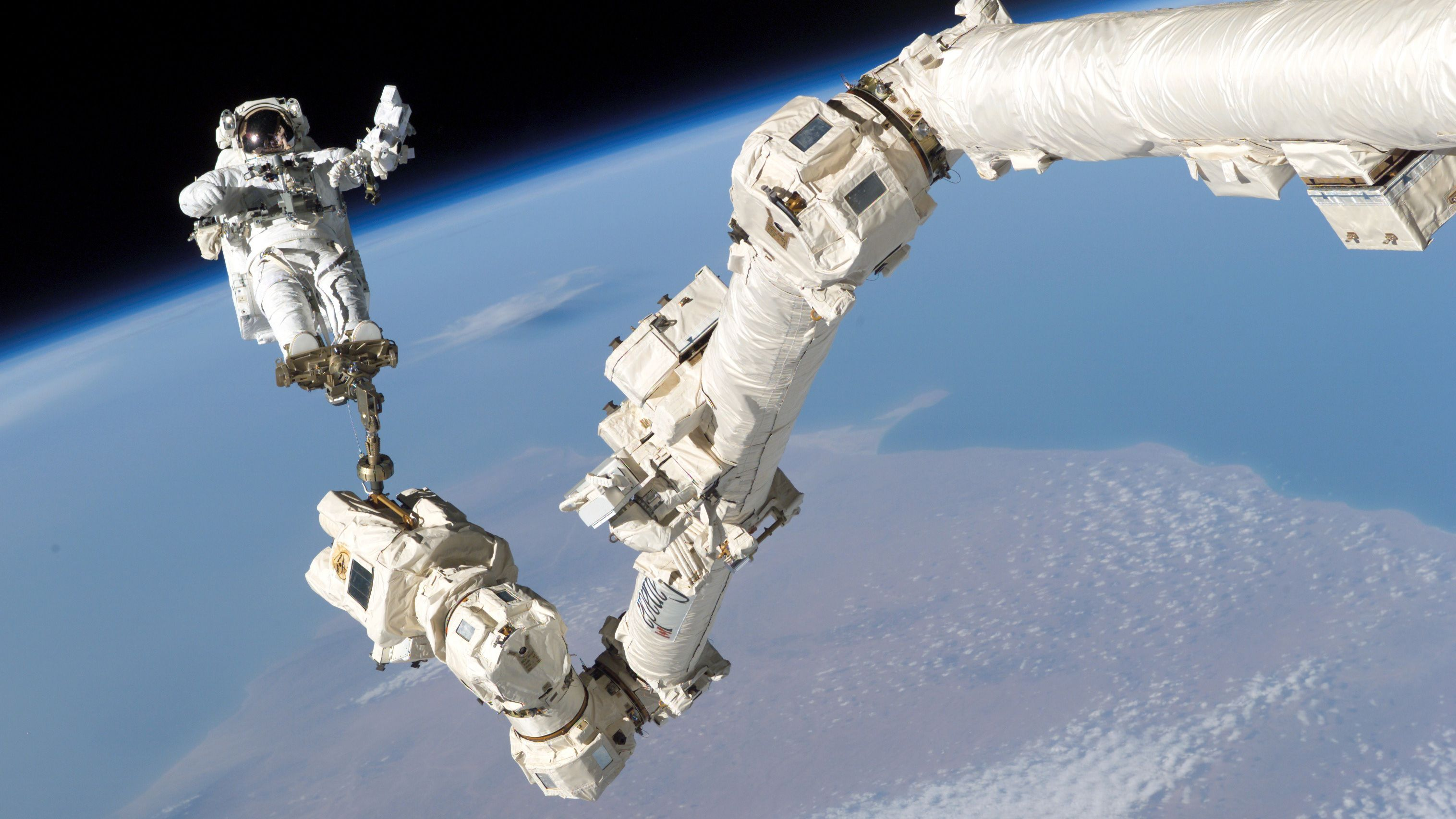 Astronaut Stephen K. Robinson, STS-114 mission specialist, anchored to a foot restraint on the International Space Station's Canadarm2, participates in the mission's third session of extravehicular activity (EVA) August 3, 2005. The blackness of space and Earth's horizon form the backdrop for the image. Picture taken August 3, 2005.