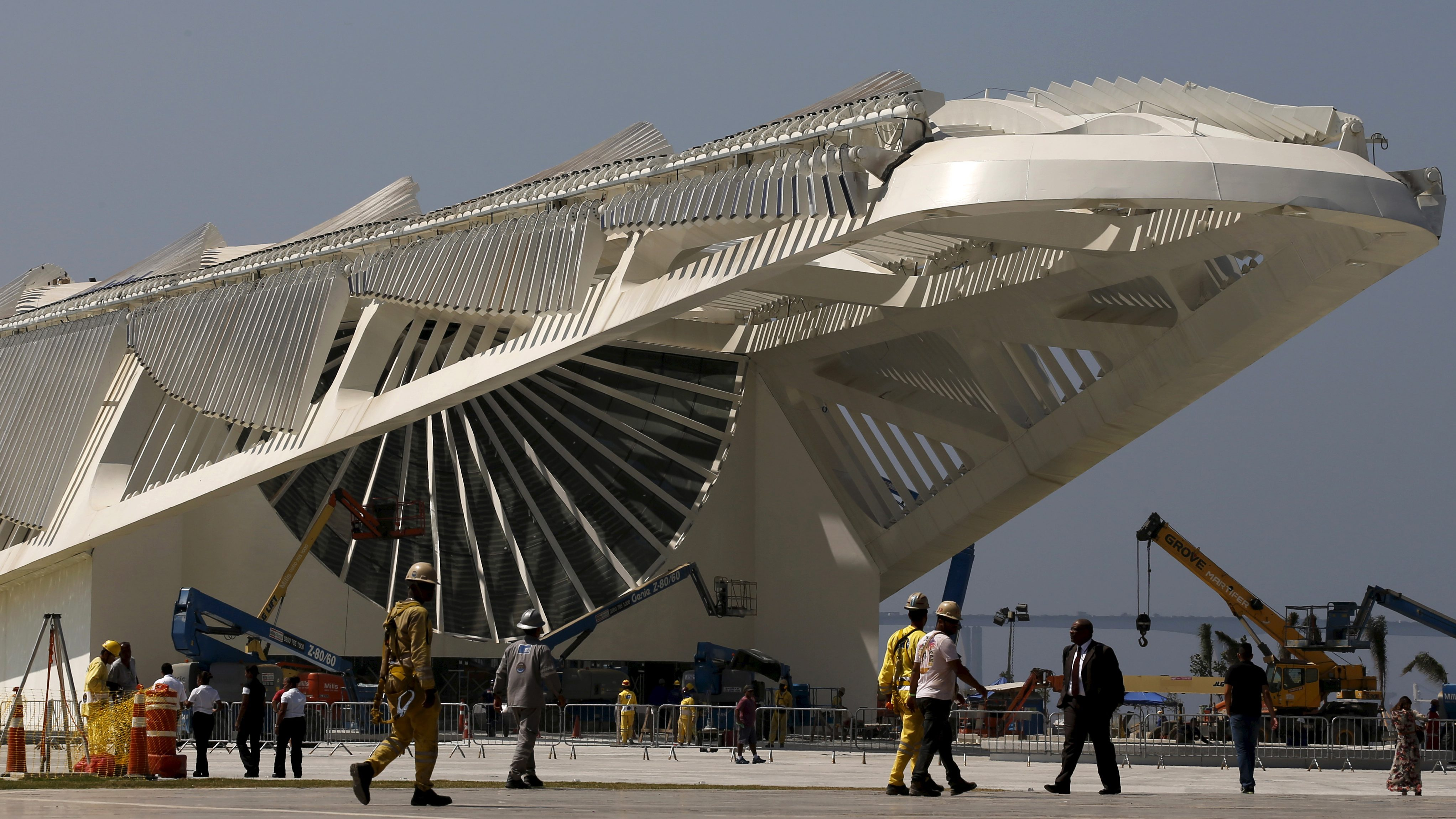 Workers walk in front of the Museu do Amanha (Museum of Tomorrow), which is under construction, at the port zone in Rio de Janeiro, Brazil, September 23, 2015. The highway has been torn down, tunnels dug, and the walkways and gardens laid in Rio de Janeiro's new business district. But the dozens of office towers needed to make the 8 billion real ($2 billion) renovation viable are missing. The transformation of a derelict port district before the 2016 Olympic Games is a flagship development that wasn't supposed to cost Brazilian taxpayers a thing. Less than a year before the Olympics, however, a real-estate meltdown in Rio has killed appetite for new skyscrapers and left a public fund - which paid upfront for infrastructure betting it could profit by selling building rights - shouldering the burden of the 8 billion real cost. Picture taken on September 23, 2015. REUTERS/Sergio Moraes - RTS2FPL