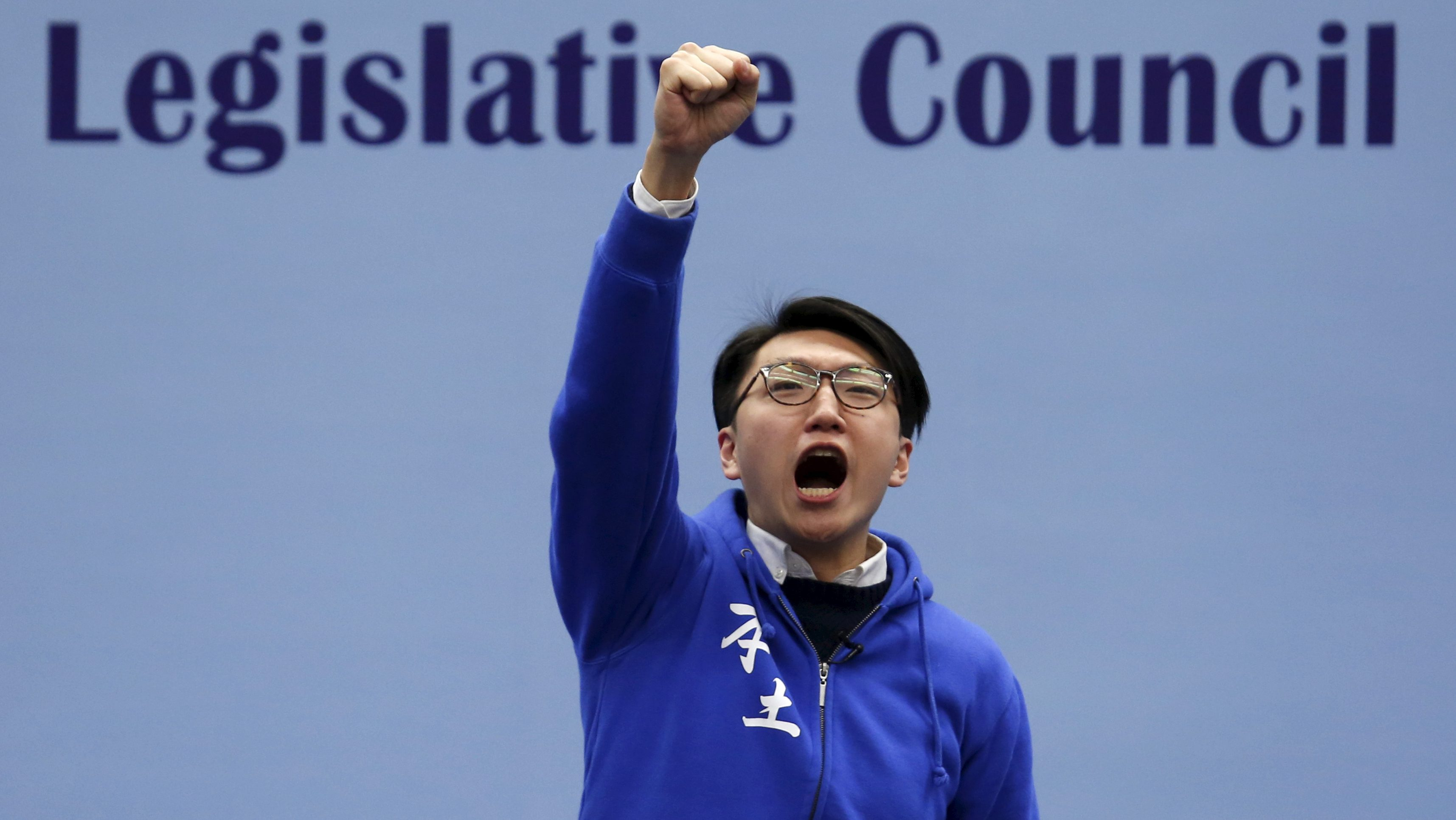 Edward Leung, a candidate from the Hong Kong Indigenous, chants slogans on the podium before the final poll result is announced in Hong Kong, China February 29, 2016, after a Legislative Council by-election on Sunday.   REUTERS/Bobby Yip - RTS8EYN
