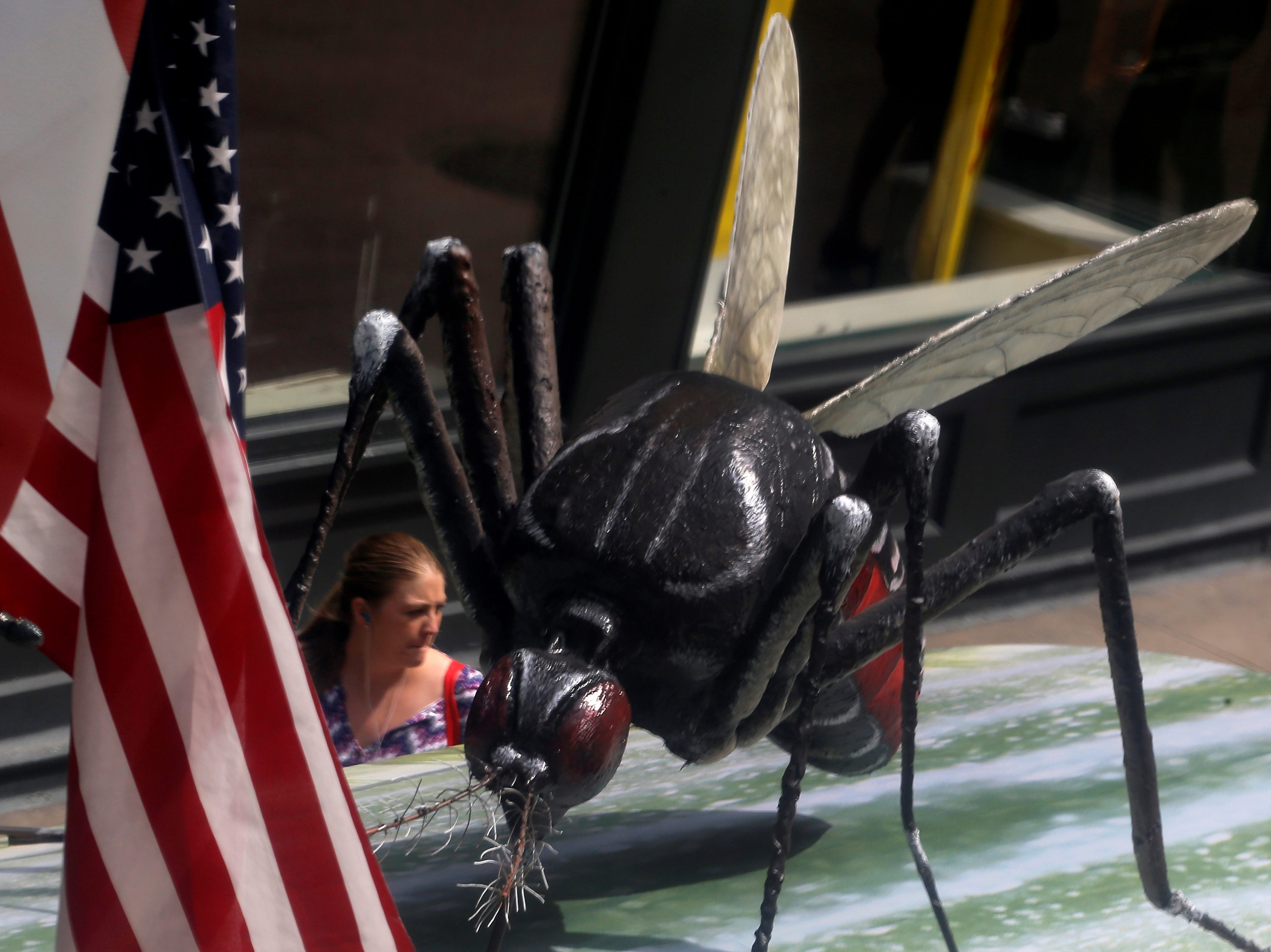A woman walks past a giant fake mosquito placed on top of a bus shelter as part of an awareness campaign about the Zika virus in Chicago, Illinois, United States, May 16, 2016. REUTERS/Jim Young