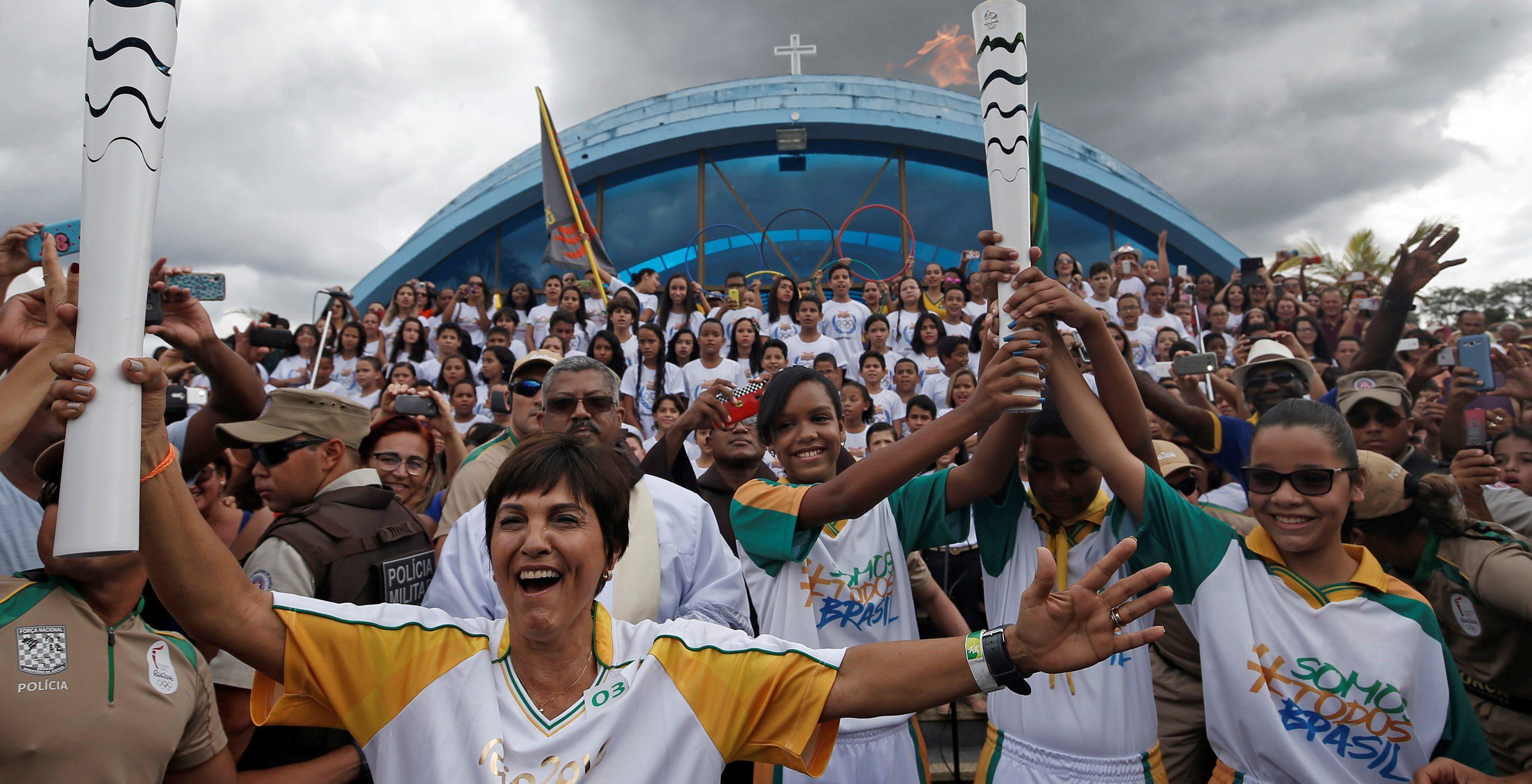 Resident Maria da Gloria takes part in the Olympic Flame torch relay in Itamaraju, Bahia state, Brazil