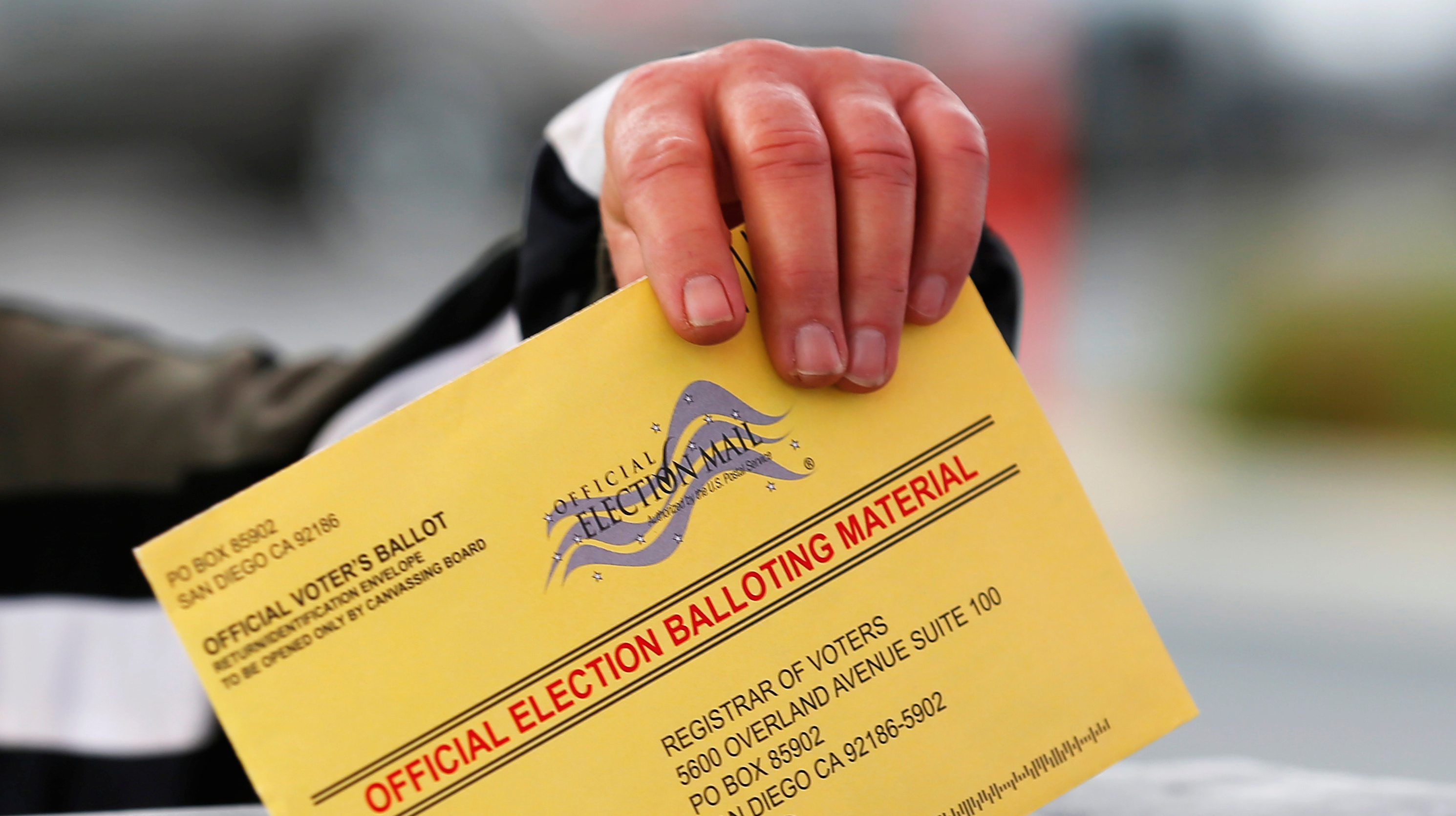 A poll worker places a mail in ballot into a voting box as voters drop off their ballot in the U.S. presidential primary election in San Diego, California
