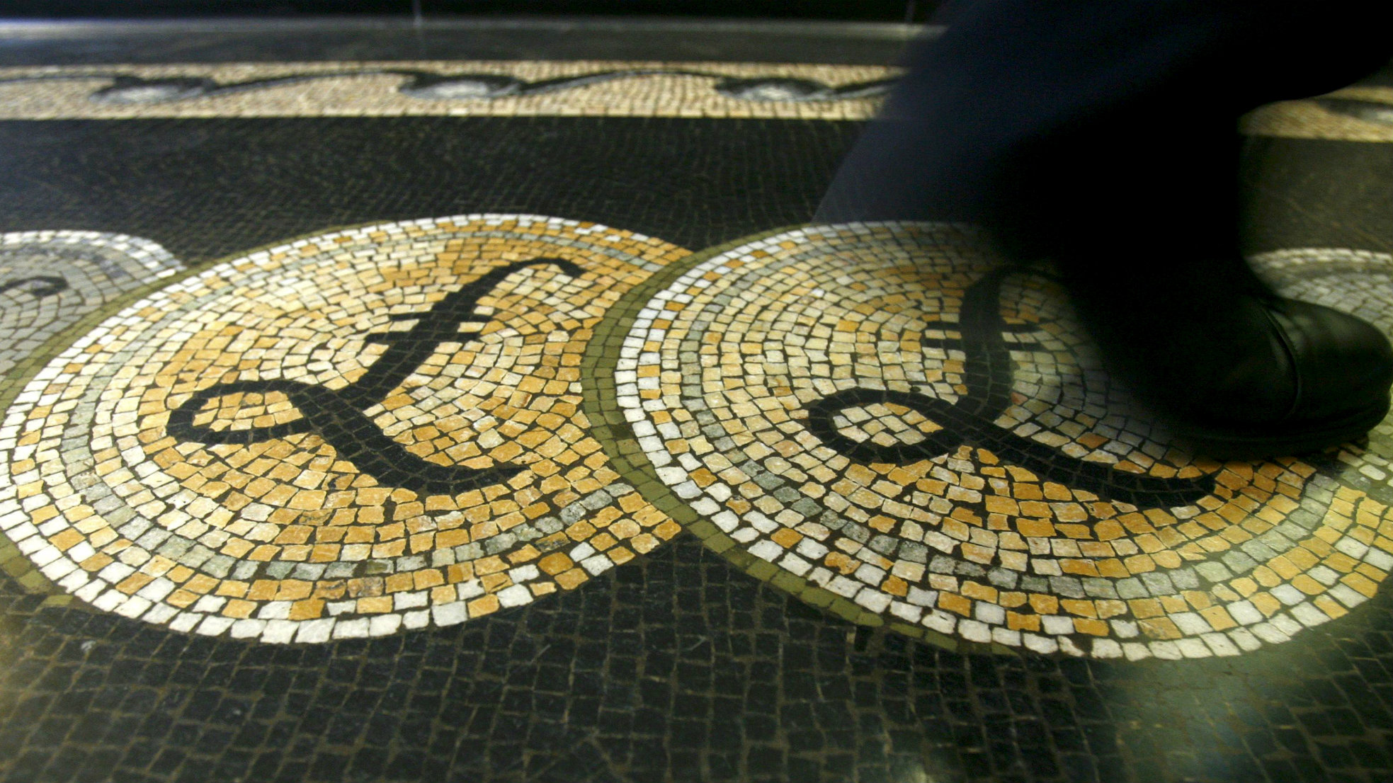 An employee is seen walking over a mosaic of pound sterling symbols set in the floor of the front hall of the Bank of England in London, Britain 25, 200