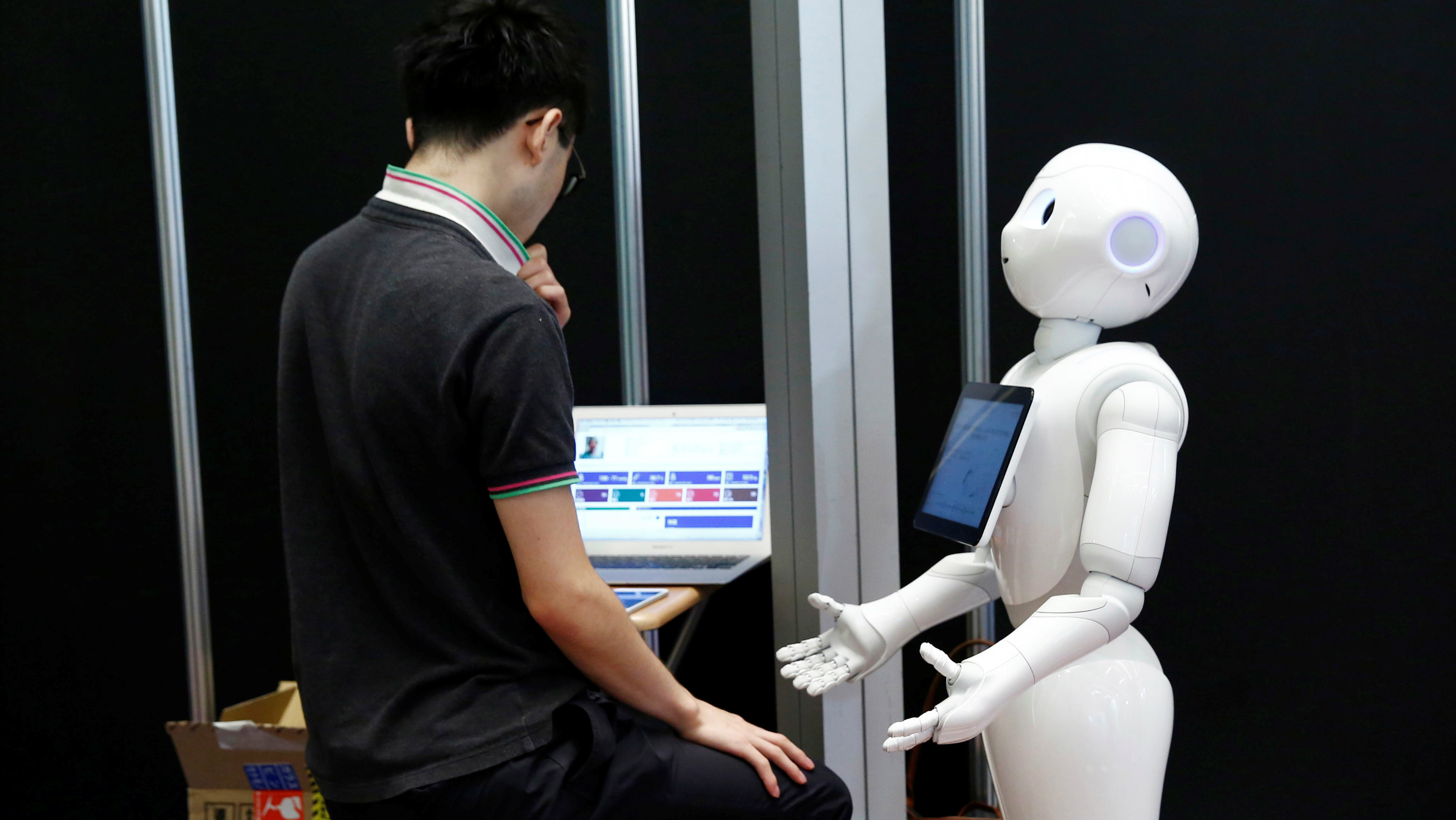 A man sets up a SoftBank humanoid robot known as Pepper as he prepares for Pepper World 2016 Summer, ahead of its opening on Thursday, in Tokyo, Japan, July 20, 2016.
