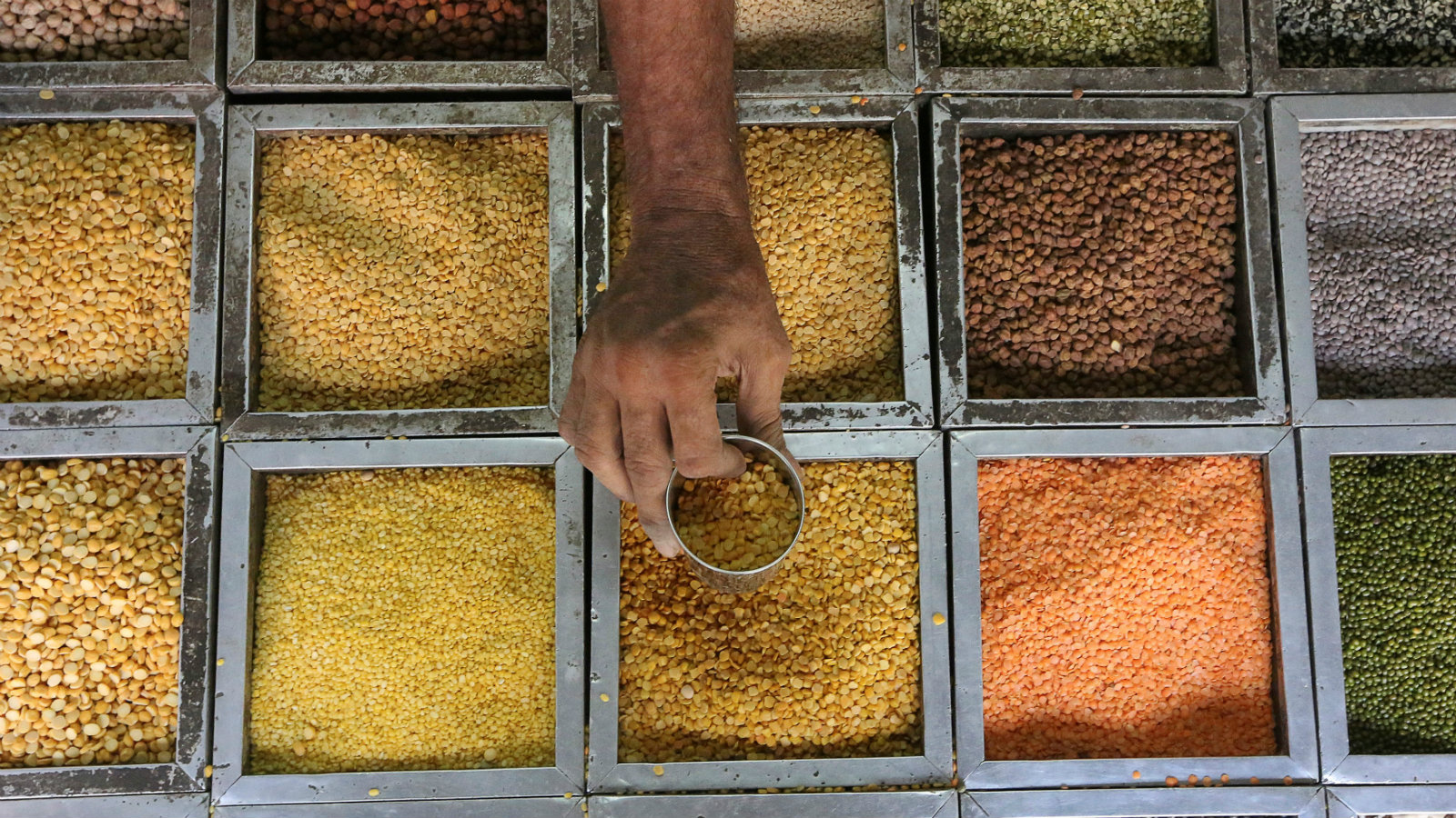 An employee collects lentils from a container inside a grocery store at a residential area in Mumbai, India, May 11, 2016.