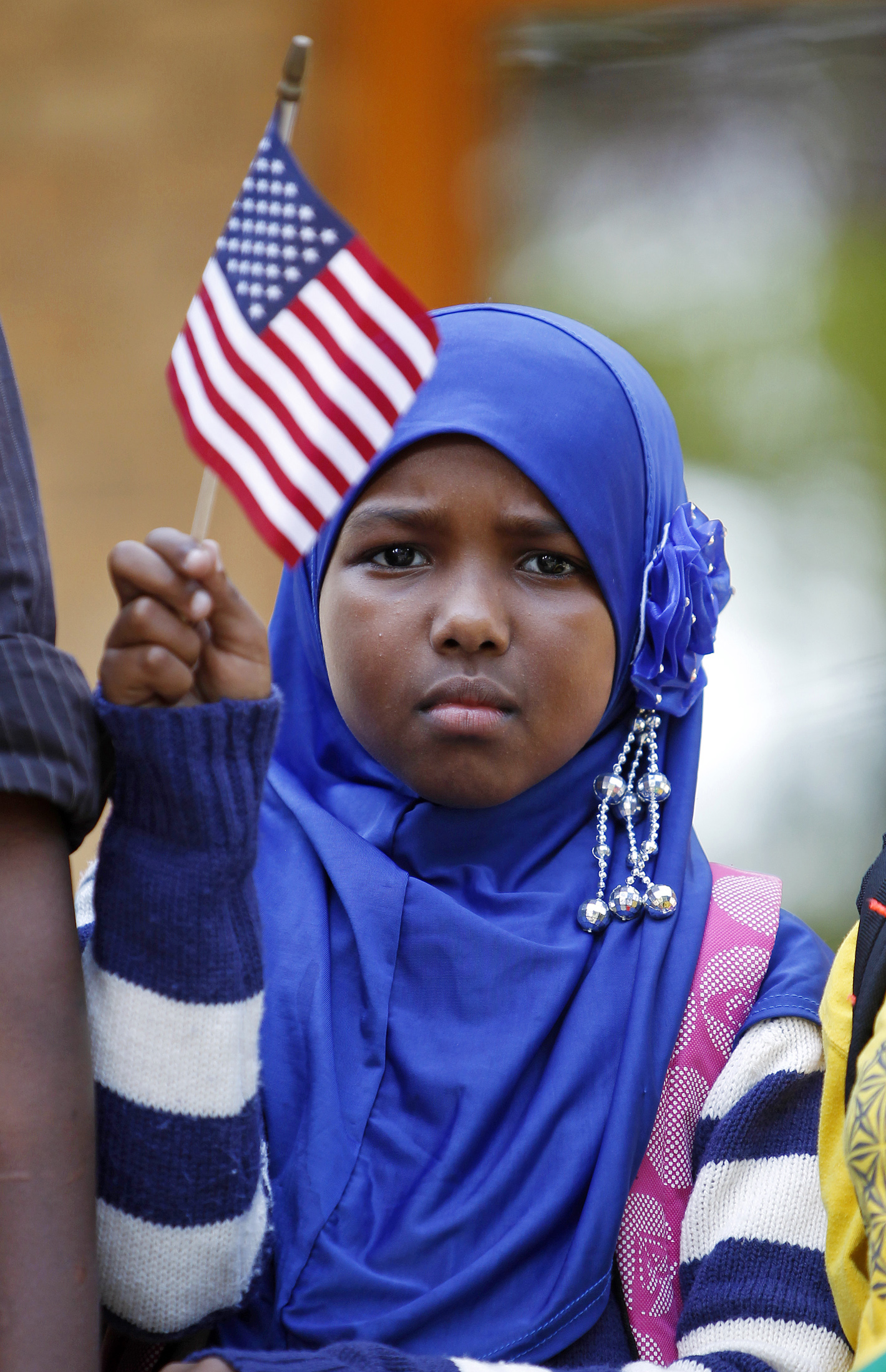 Ilhan Issa, a Somali-American girl from Minneapolis, waves an American flag.