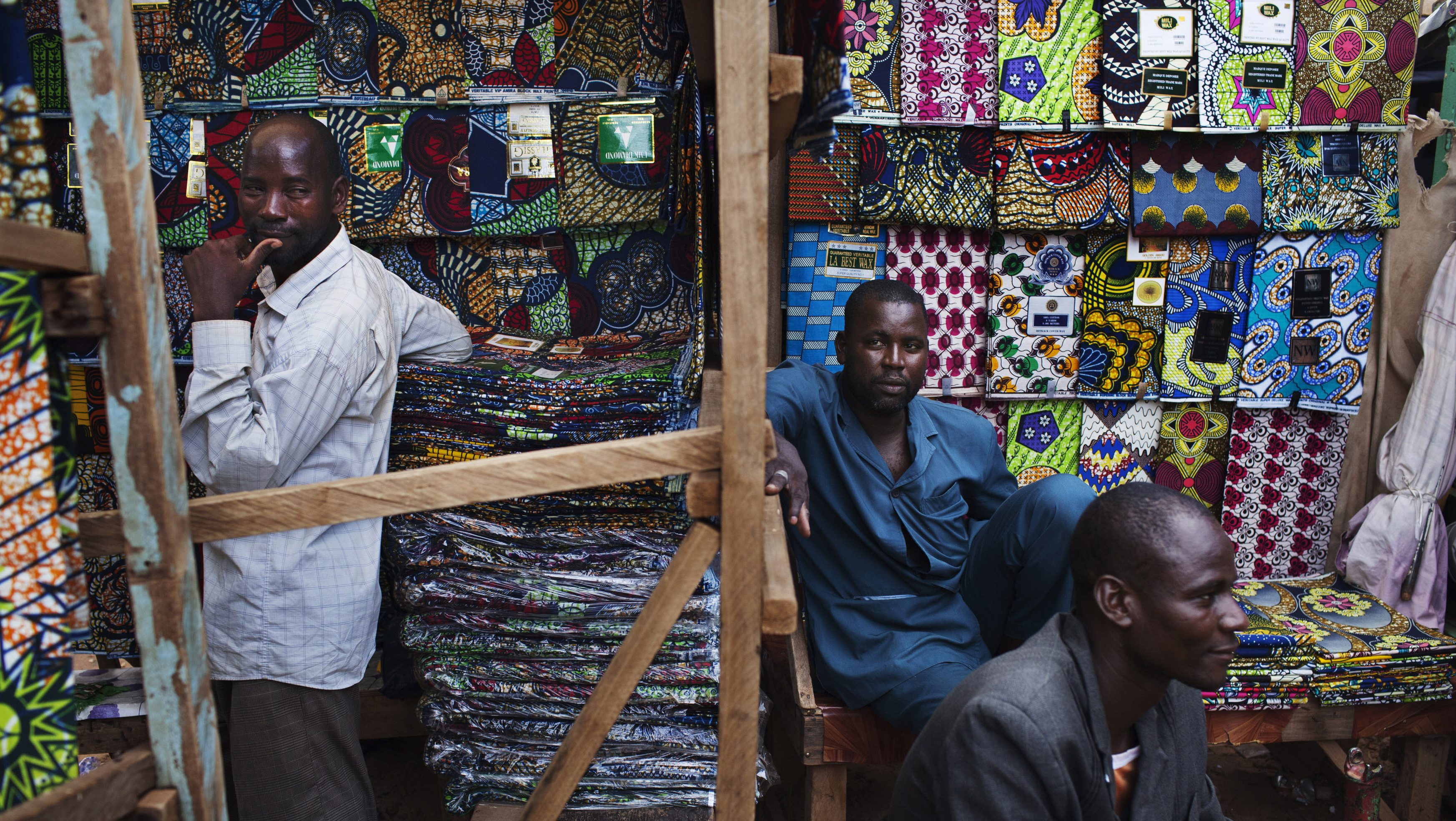 Cloth vendors sit in front of wax cloth for sale at the Grand Market in Niamey, September 17, 2013. Picture taken September 17, 2013.  To match Special Report NIGER-AREVA/              REUTERS/Joe Penney (NIGER - Tags: BUSINESS EMPLOYMENT SOCIETY TEXTILE) - RTX1895V