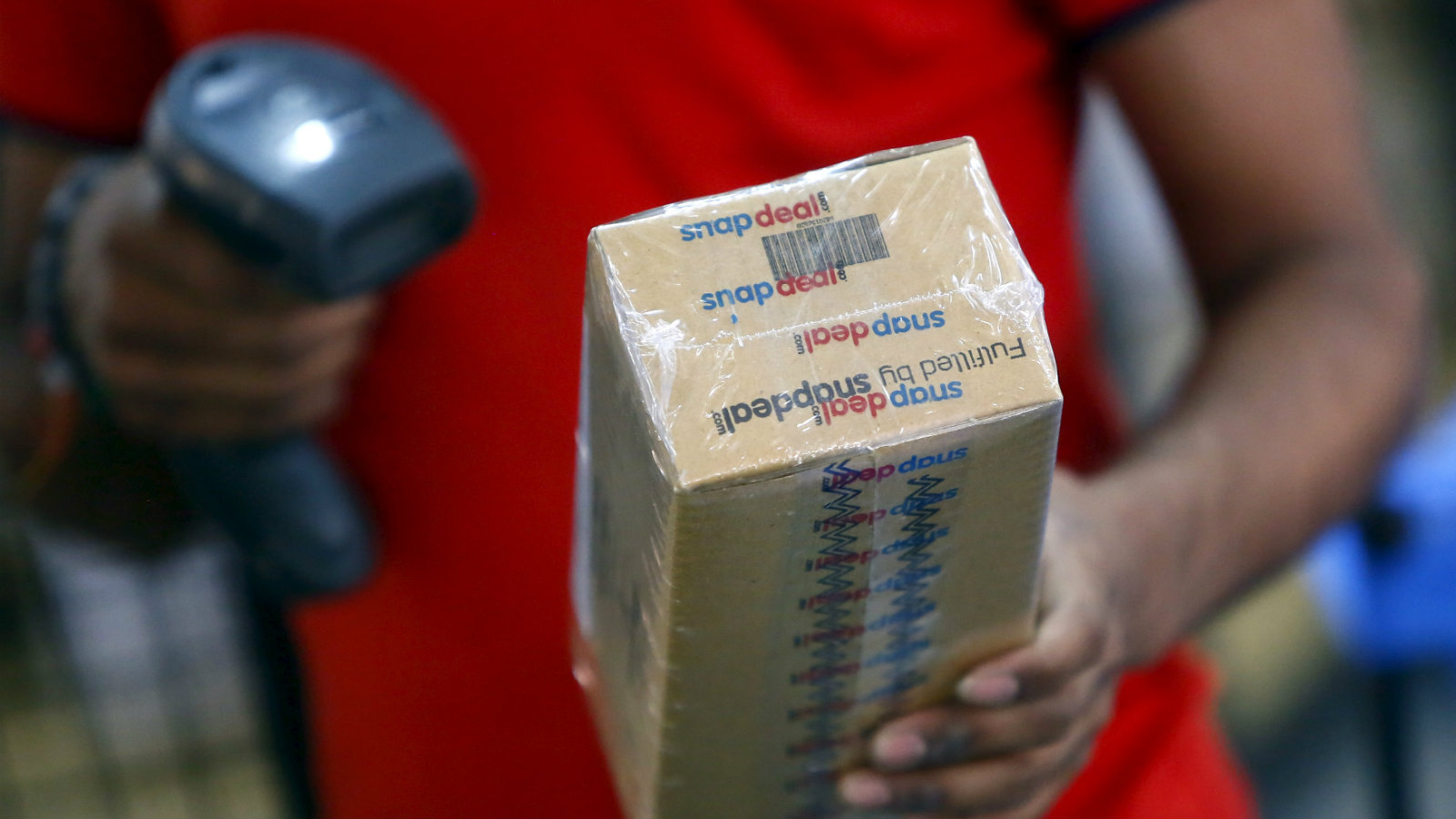 A worker of Indian e-commerce company Snapdeal.com scans barcode on a box after it was packed at the company's warehouse in New Delhi April 20, 2015. After losing top engineering talent for years to America's tech heartland of Silicon Valley, India is luring them back as an e-commerce boom sparks a thriving start-up culture, unprecedented pay, and perks including free healthcare for in-laws. Picture taken April 20, 2015. To match INDIA-ECOMMERCE/WORKERS.