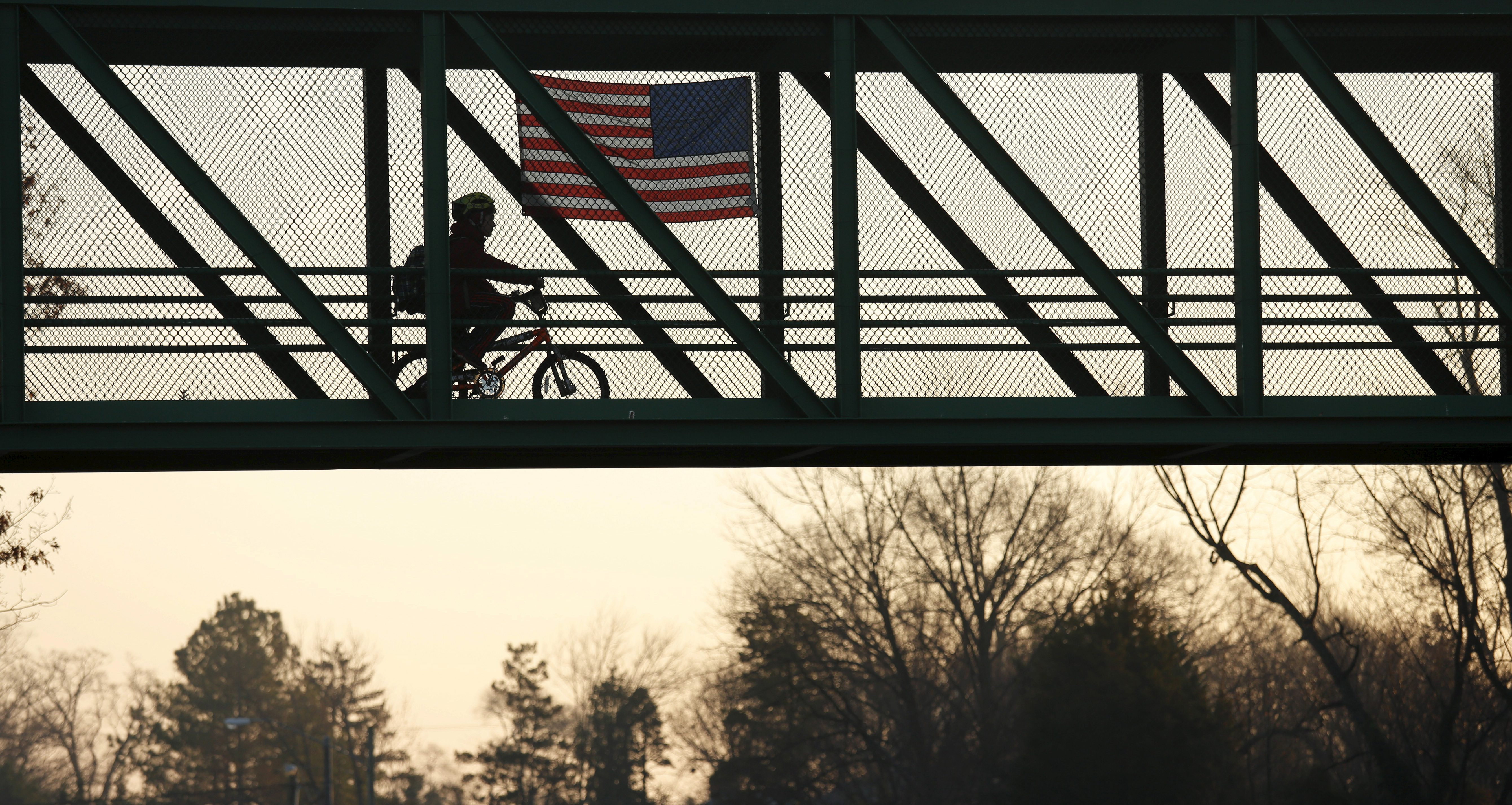 A boy riding his bicycle to school passes a U.S. flag placed upon a highway overpass in Arlington, Virginia, just outside of Washington