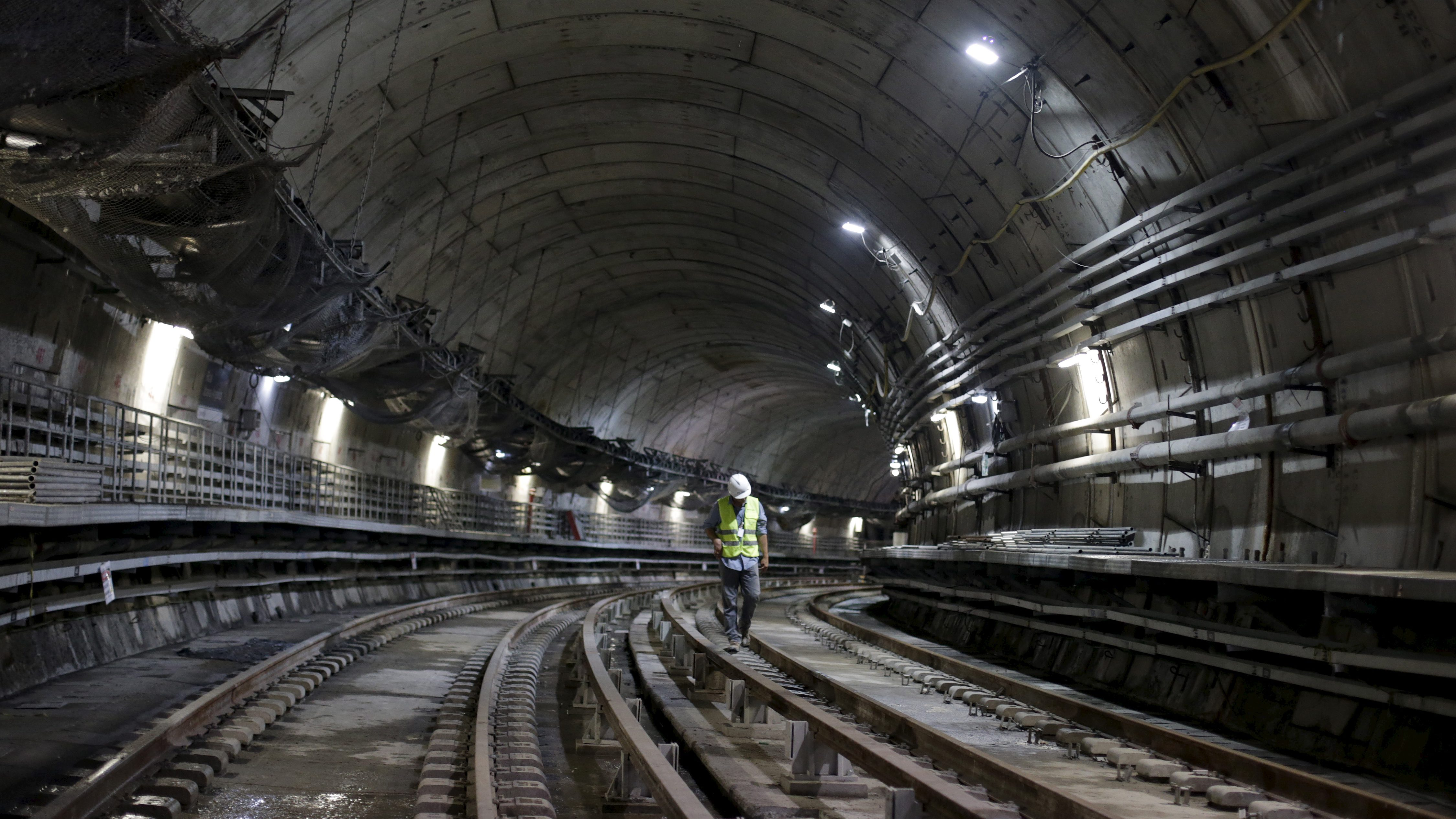 A man walks on the railroad of a metro line extension under construction near Nossa Senhora da Paz station in Rio de Janeiro, Brazil, February 24, 2016. The extension, which will connect Rio de Janeiro's Olympic Park in Barra de Tijuca with the rest of the city, is at risk of not being finished before the Games start in August, if a delayed development bank loan is not disbursed, two senior government sources told Reuters on Monday. REUTERS/Ricardo Moraes - RTX28DN1
