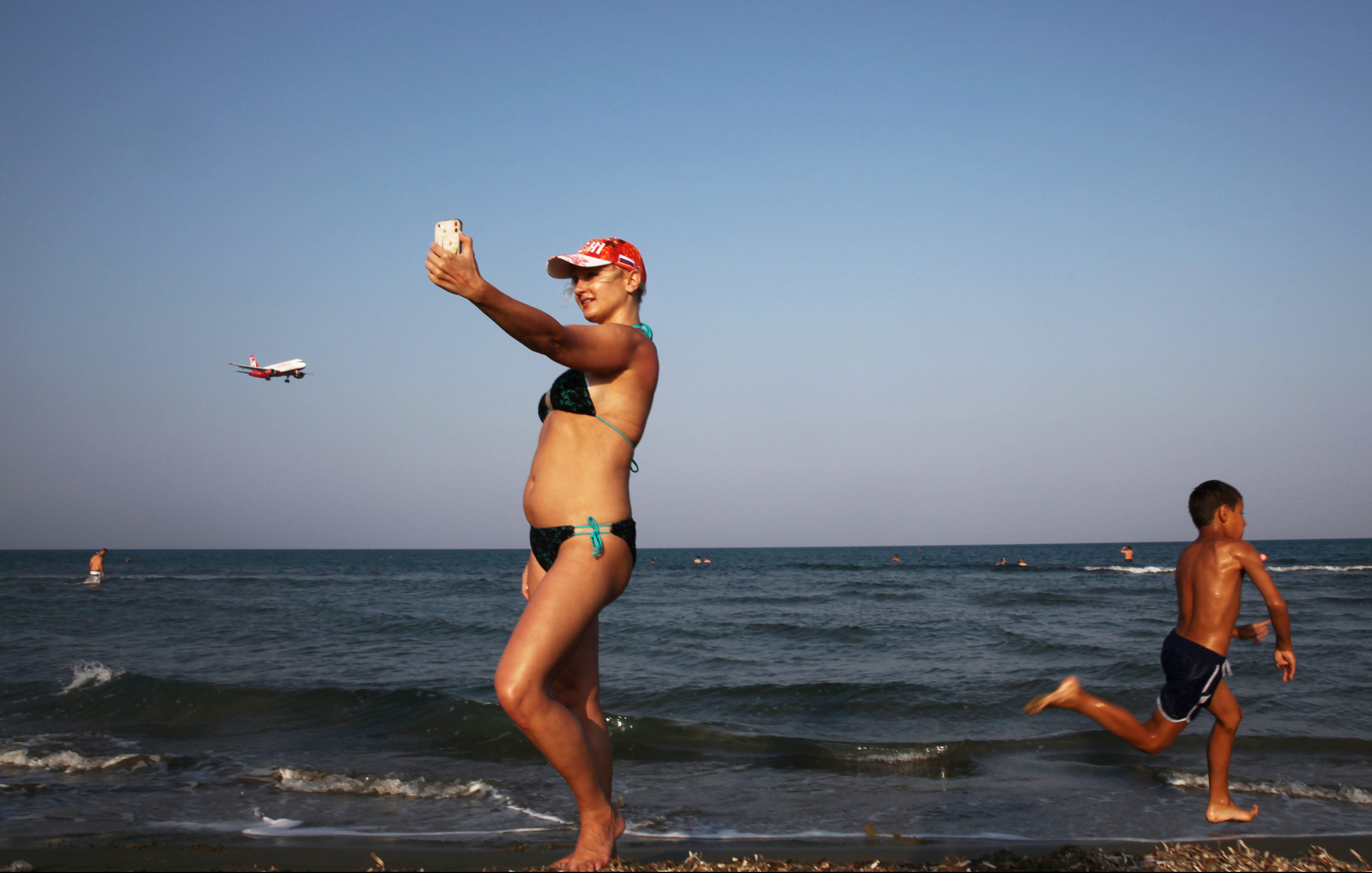 A tourist takes a selfie on a beach while an  airplane prepares to land at Larnaca International Airport