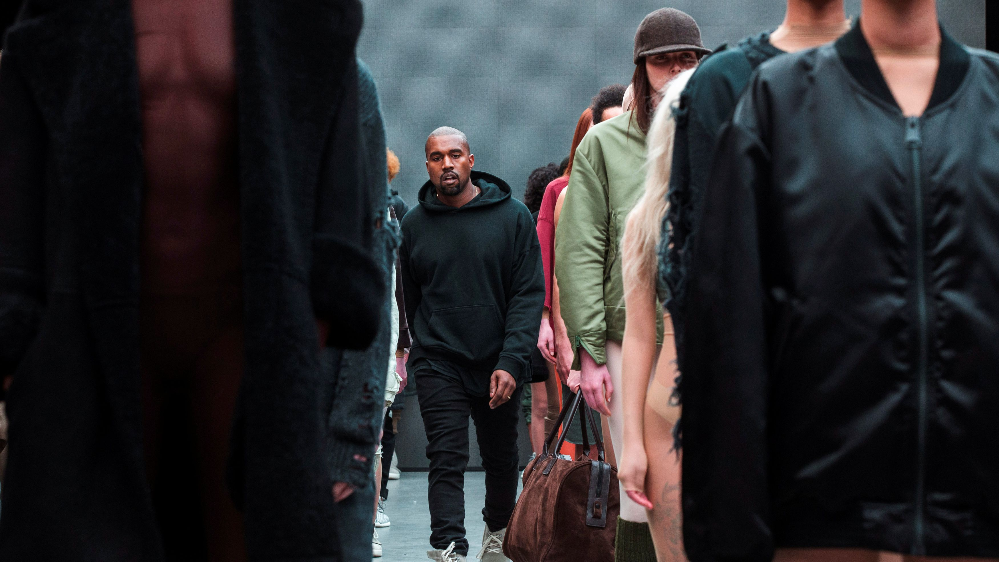 Singer Kanye West walks past models after presenting his Fall/Winter 2015 partnership line with Adidas at New York Fashion Week, U.S. February 12, 2015. Picture taken February 12, 2015.