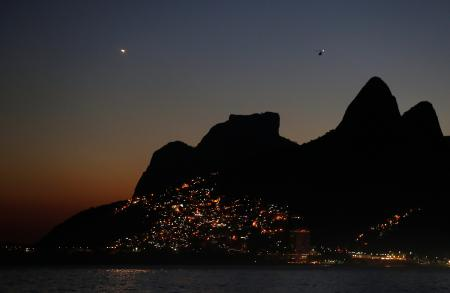 The lights of Vidigal favela are seen with the Dois Irmaos (Two brothers) peaks in Rio de Janeiro, Brazil July 4, 2016. REUTERS/Pawel Kopczynski - RTX2JPHS