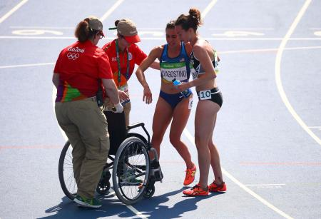 2016 Rio Olympics - Athletics - Preliminary - Women's 5000m Round 1 - Olympic Stadium - Rio de Janeiro, Brazil - 16/08/2016. Abbey D'Agostino (USA) of USA is helped by Nikki Hamblin (NZL) of New Zealand after finishing the race. Hamblin helped the injured D'Agostino get back up on the track during the race. REUTERS/David Gray FOR EDITORIAL USE ONLY. NOT FOR SALE FOR MARKETING OR ADVERTISING CAMPAIGNS. - RTX2L74R