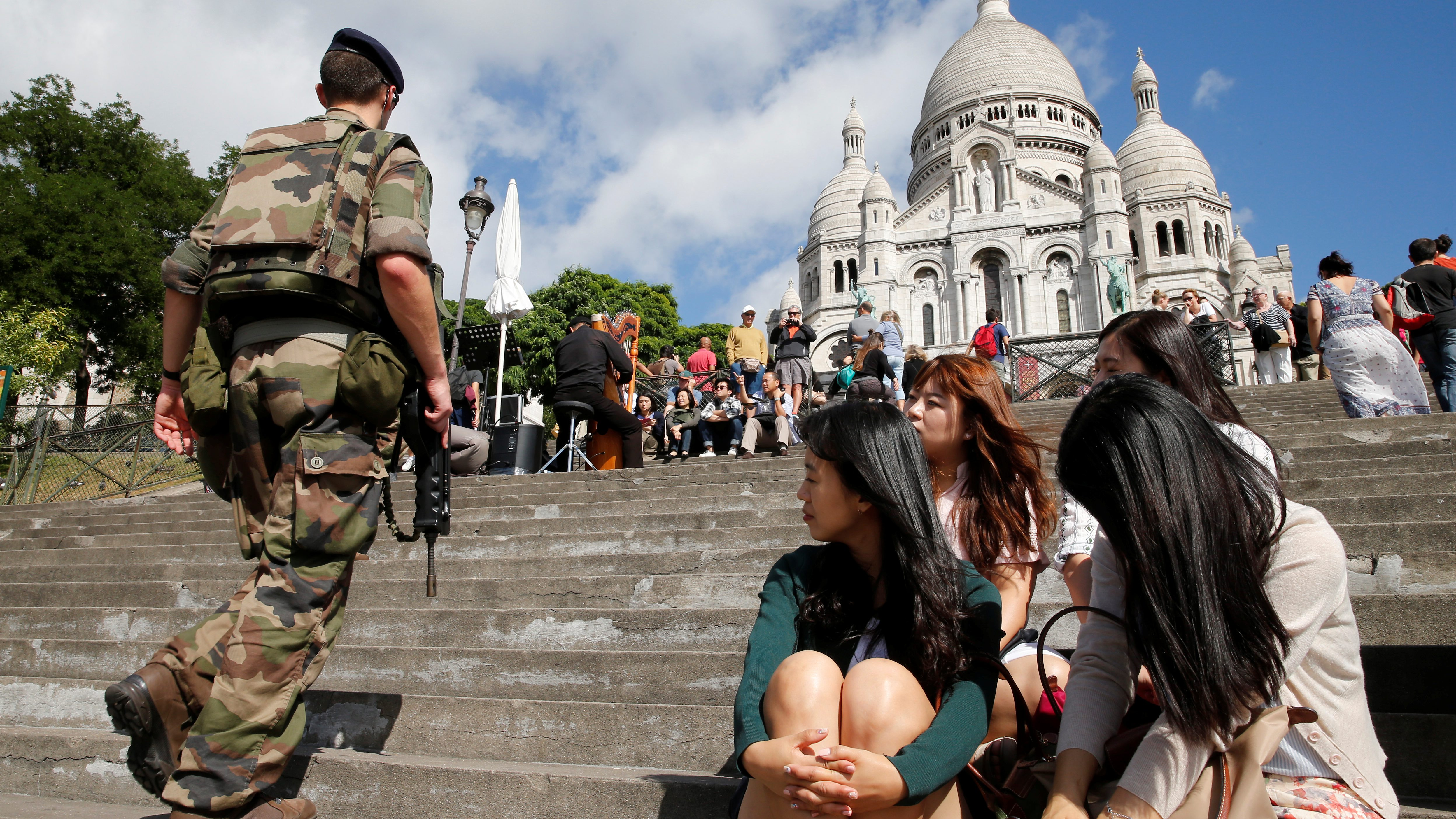 French soldier patrols under the gaze of Korean tourists at Montmartre's Sacre Coeur Church in Paris