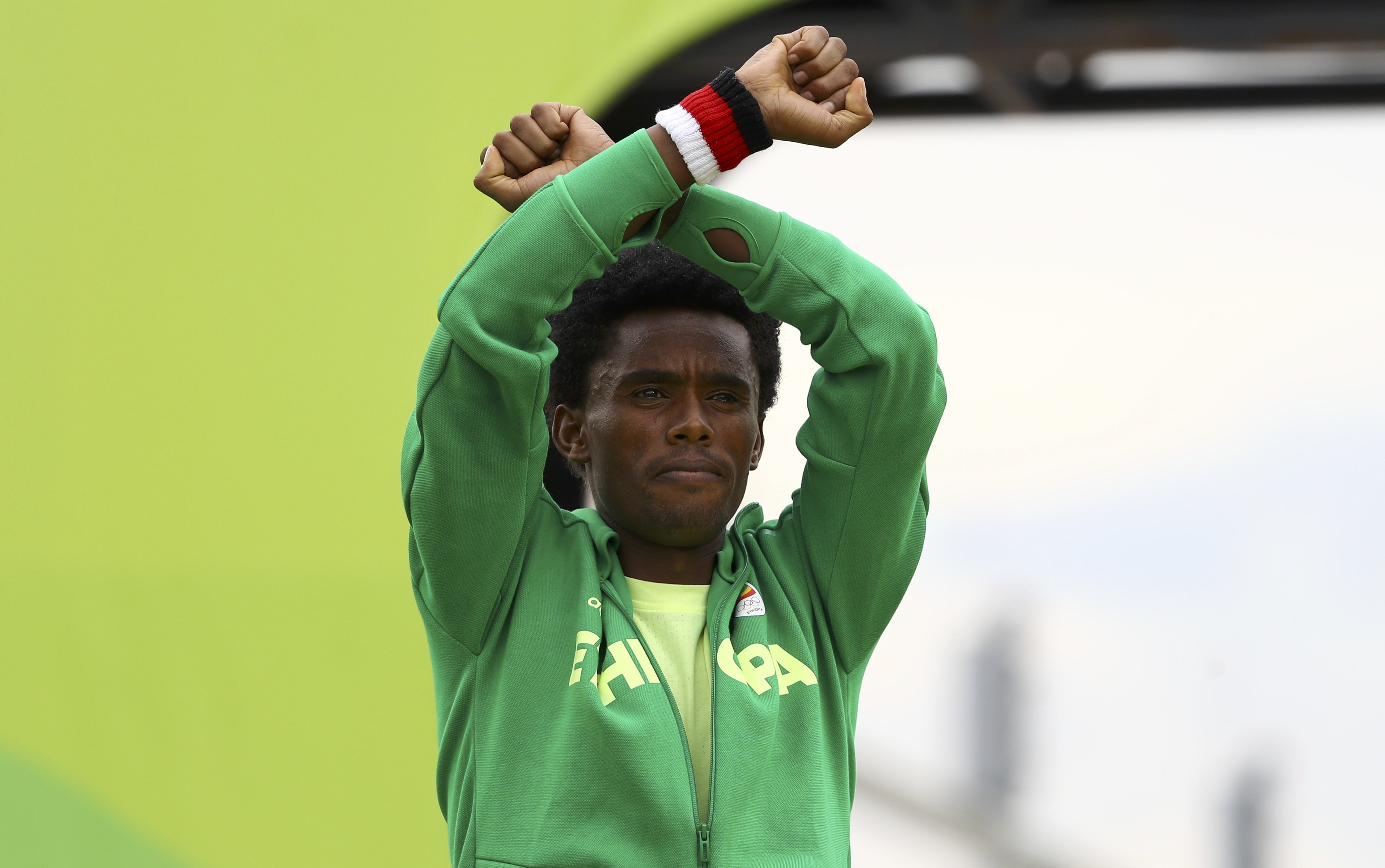 Ethiopia's Feyisa Lilesa crosses his wrists to protest Ethiopian government's crackdown on Oromo people.