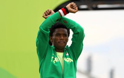 Ethiopia's Feyisa Lilesa crosses his wrists to protest Ethiopian government's crackdown on Oromo people.