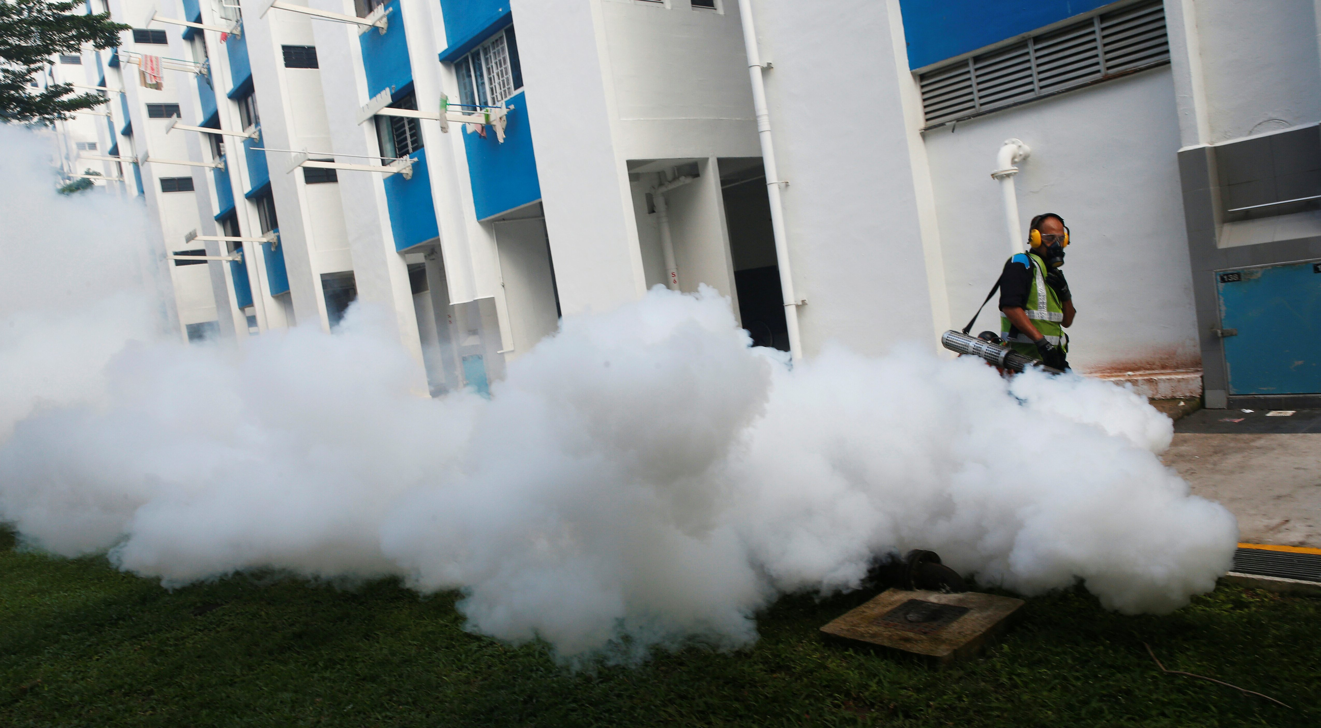 A worker fogs the drains in the common areas of a public housing estate at an area where locally transmitted Zika cases were discovered in Singapore