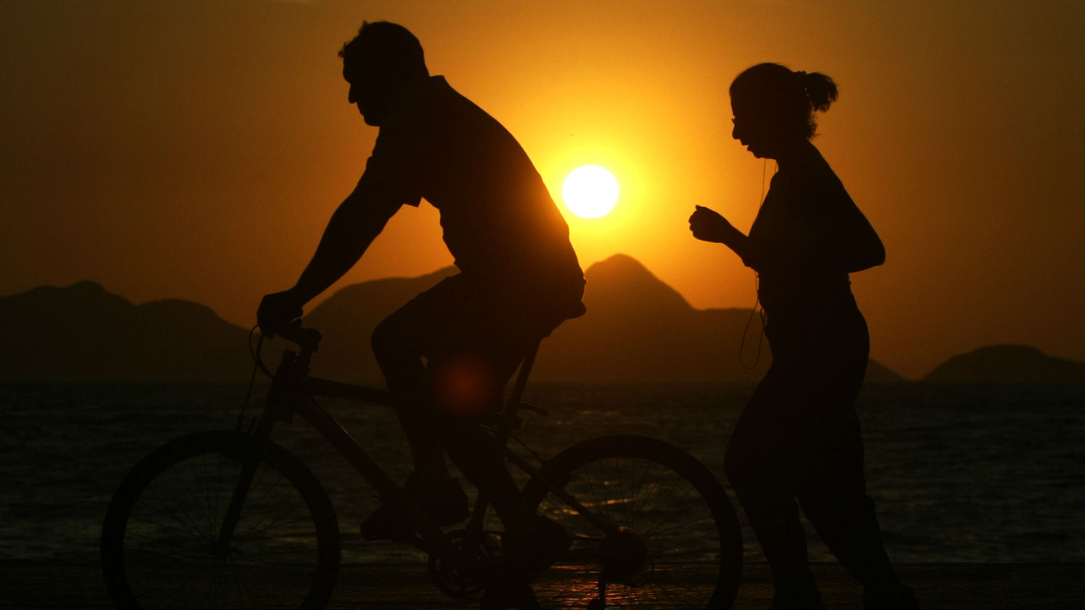 A runner goes for a jog as a cyclist passes by during sunrise on Copacabana beach marking the start a new day in Rio de Janeiro, September 15, 2004. Daytime temperatures in Rio are expected to reach 25 Celsius (77 Fahrenheit).