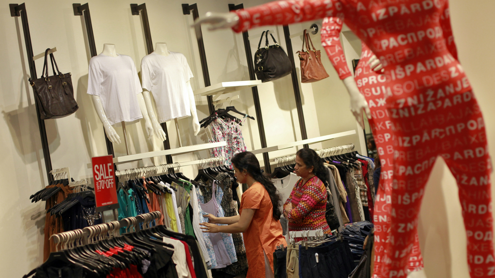 People shop for clothes during a seasonal sale at a store inside a shopping mall in Mumbai July 14, 2012.