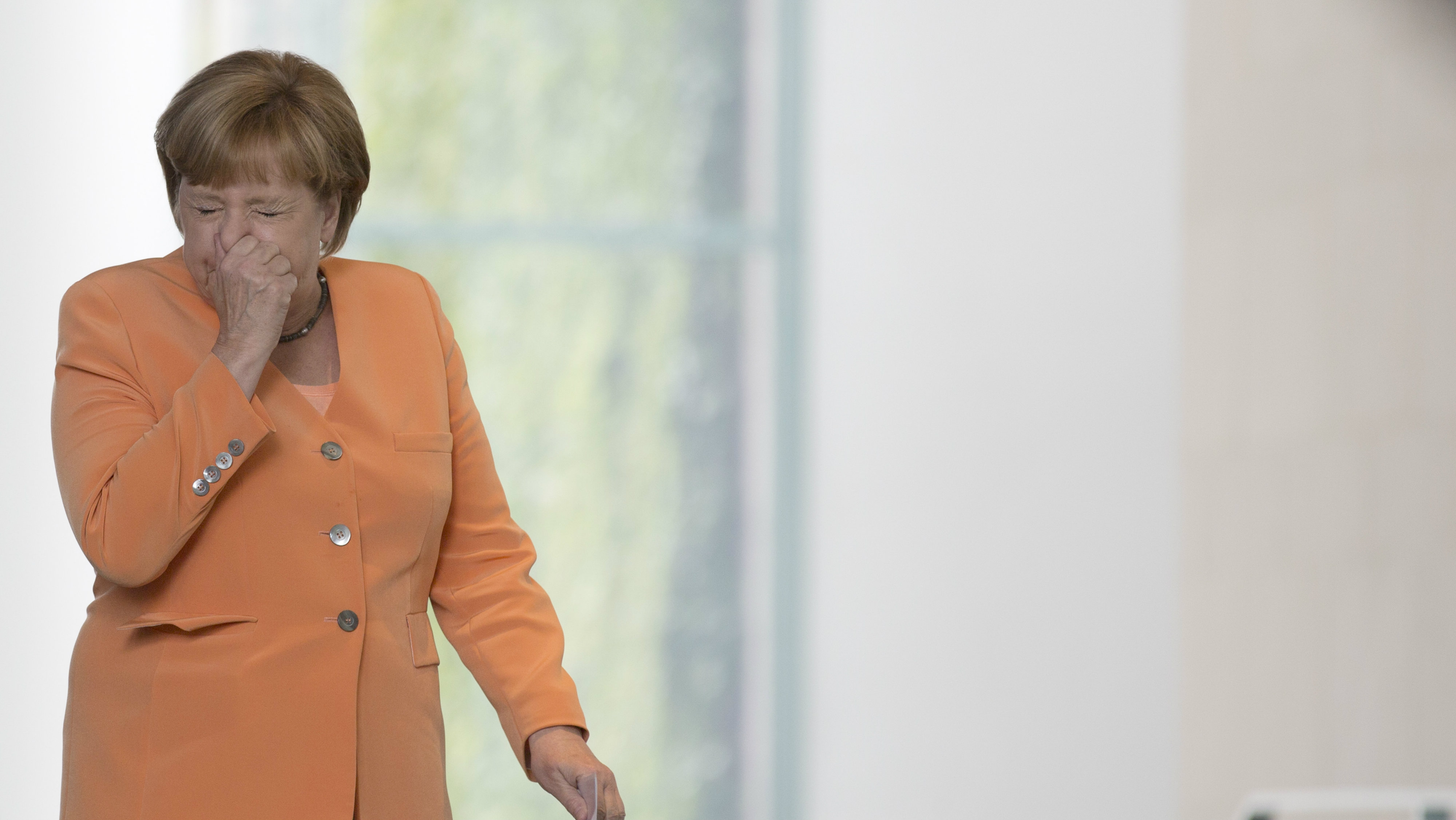 German Chancellor Angela Merkel sneezes on her way to a press conference with Slovenian Prime Minister Alenka Bratusek, unseen, in Berlin, Germany,