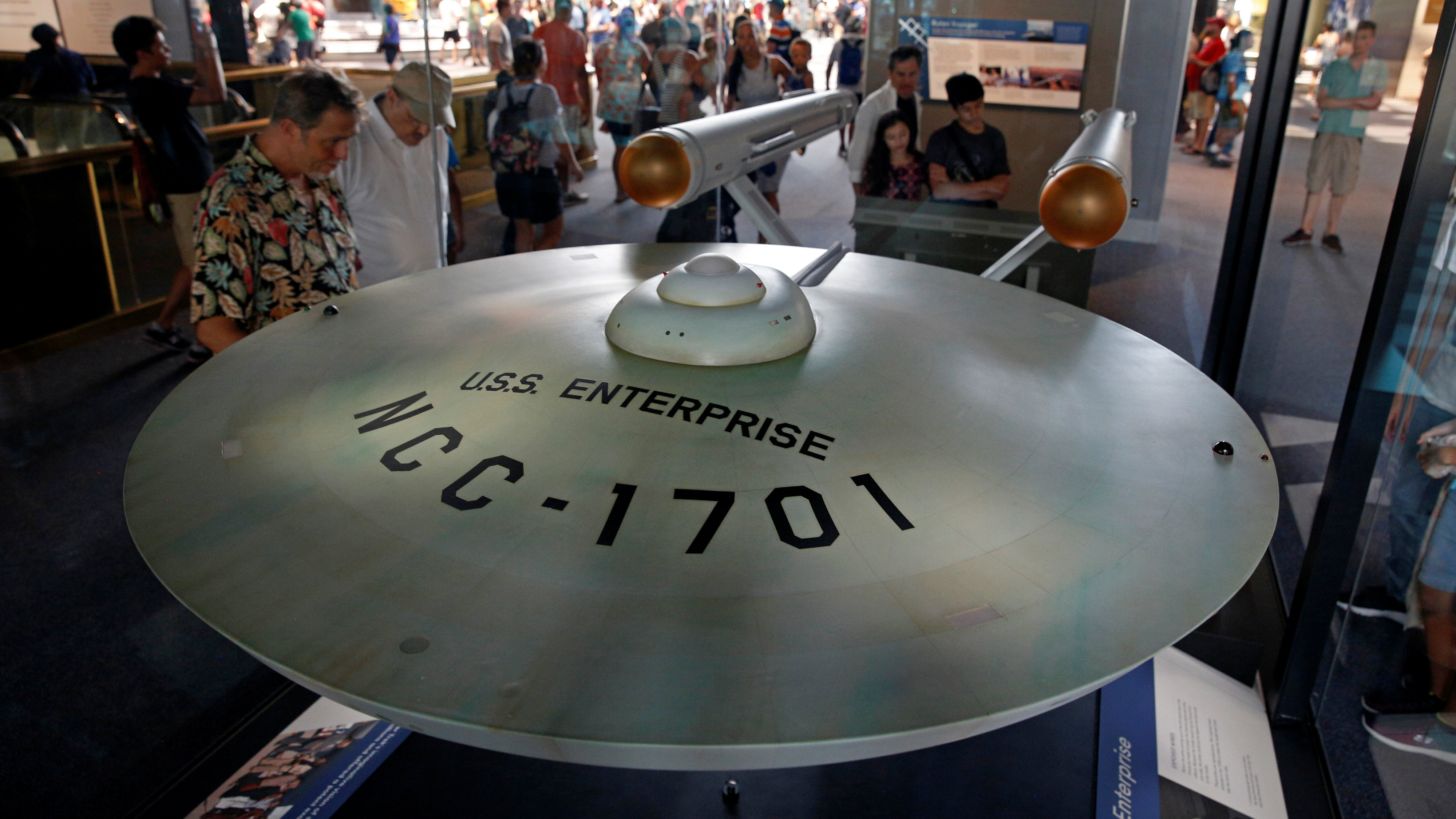 "Visitors to the Smithsonian Air and Space Museum see the fully restored original USS Enterprise model from the 1960s ""Star Trek"" TV series in Washington July 7, 2016. The USS Enterprise is one of the highlights in the museum's newly renovated and reopened Boeing Milestones of Flight Hall, coinciding with the 40th anniversary of the museum."