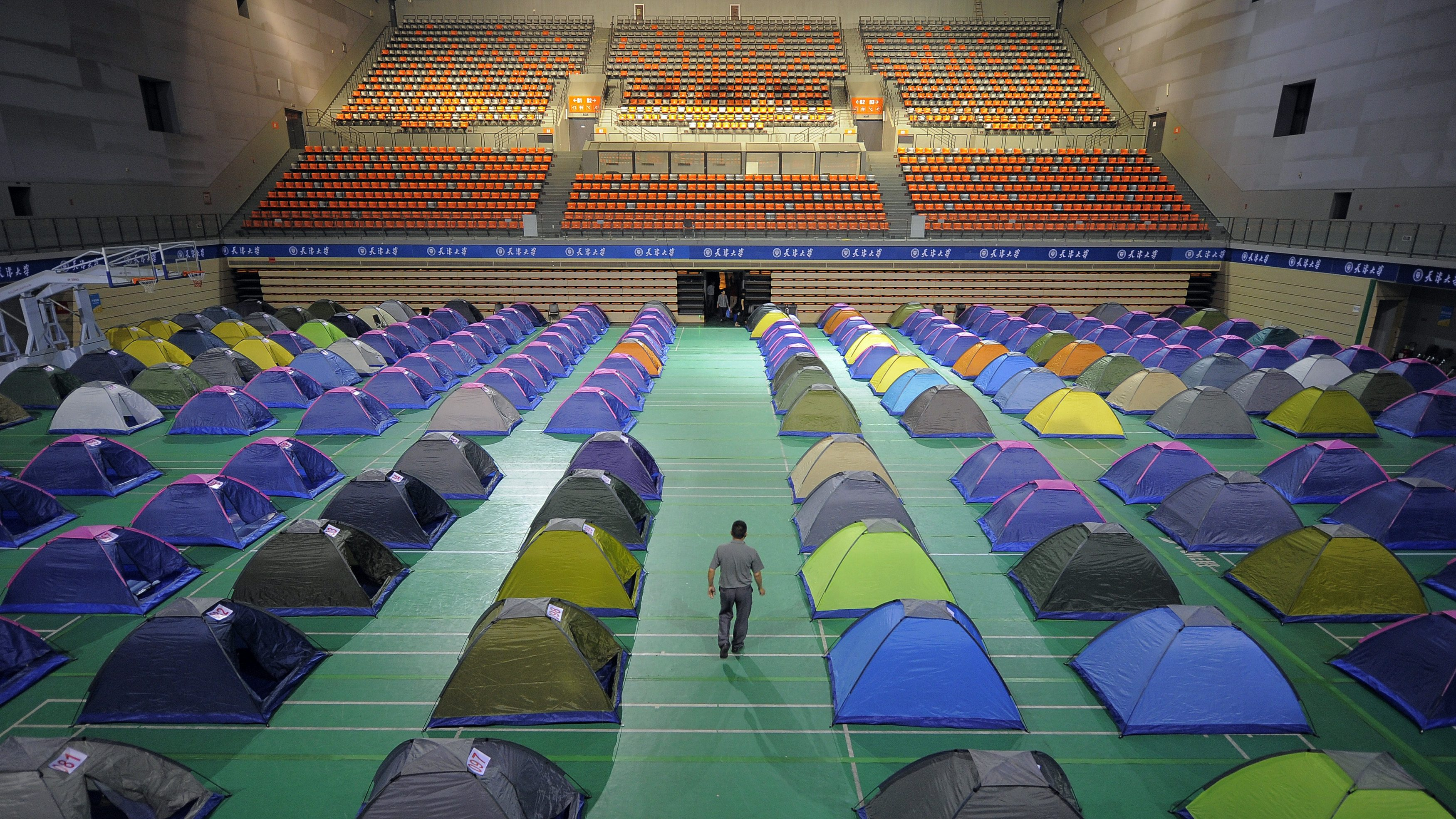 A man walks amidst tents set up on the floor of a gymnasium for parents of freshmen students at Tianjin University in Tianjin municipality, September 3, 2014. The university set up at least 270 tents in the gymnasium for the parents to stay overnight for free, local media reported. Picture taken September 3, 2014.