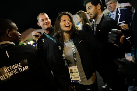 Refugee Olympic Team's Yusra Mardini, center, smiles during a welcome ceremony held at the Olympic village ahead of the 2016 Summer Olympics in Rio de Janeiro, Brazil, Wednesday, Aug. 3, 2016.