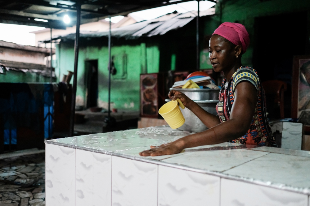 A woman wiping down the serving counter at the end of the day at a popular chop bar at Atwemonom.