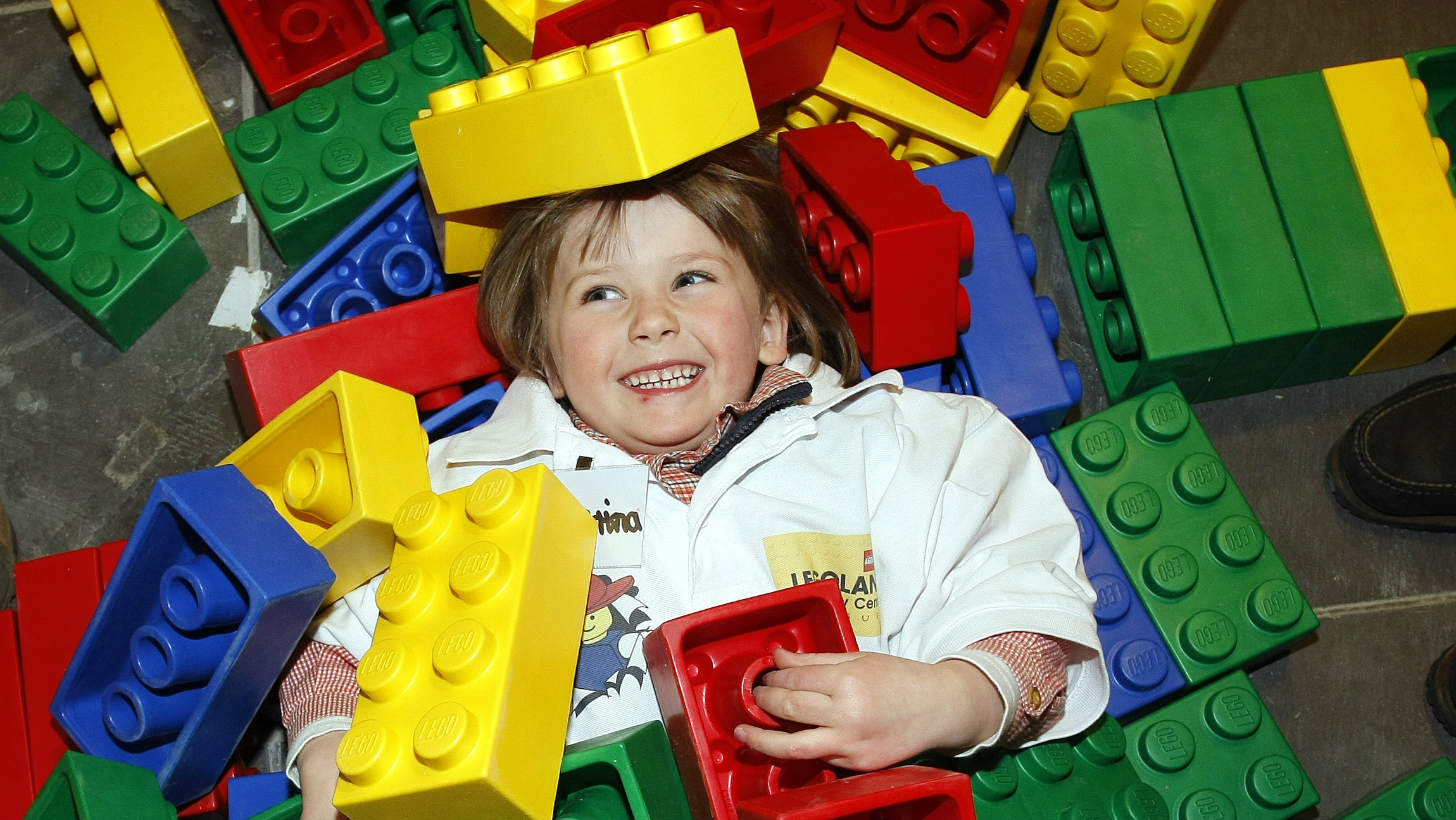 A girl plays with oversized legos.