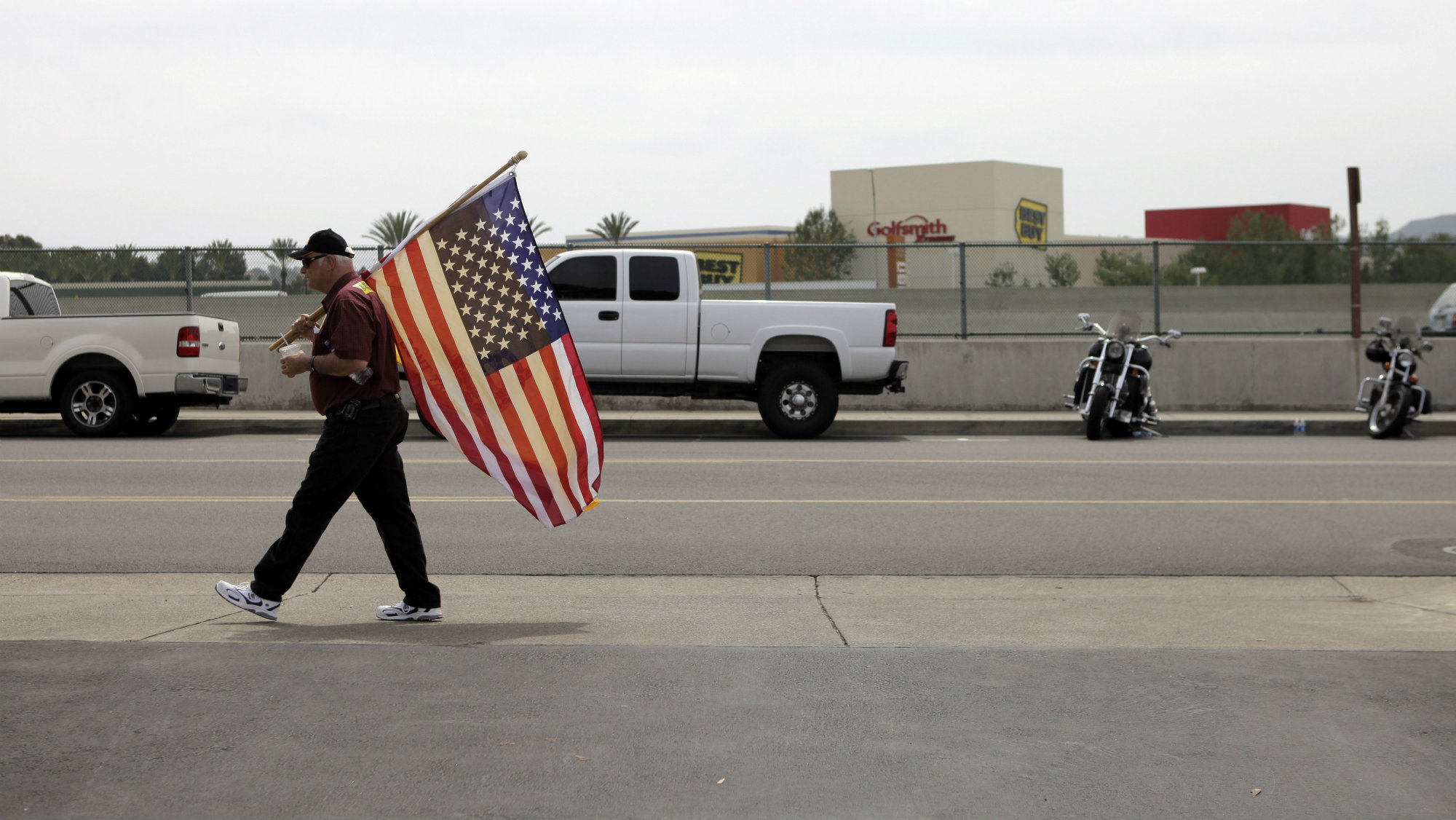 A man walks along the street with an American flag