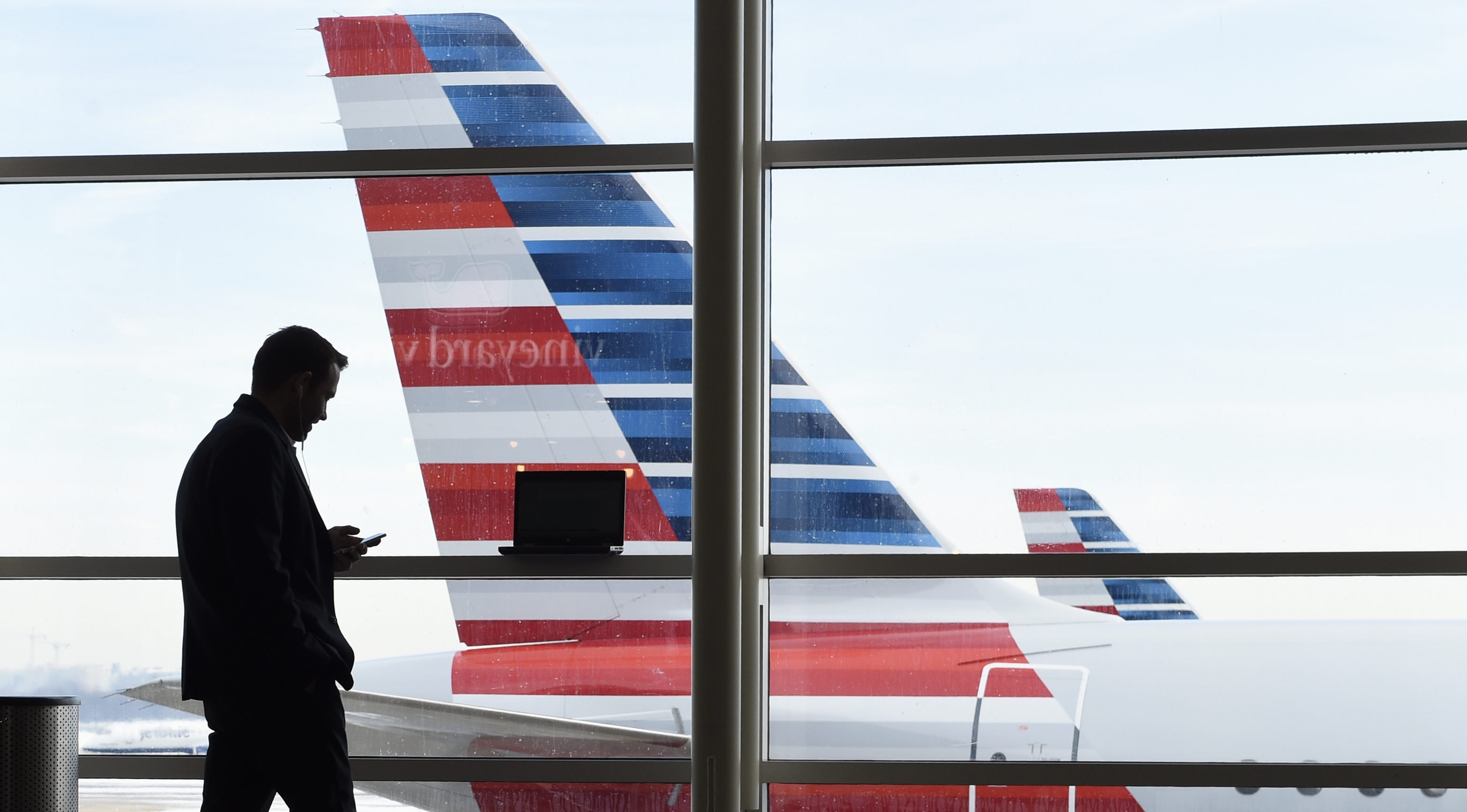 FILE - In this Jan. 25, 2016, file photo, a passenger talks on the phone as American Airlines jets sit parked at their gates at Washington's Ronald Reagan National Airport. American Airlines is giving more details on changes that will reward the highest-paying passengers, not just those who fly the most miles, announcing Monday, June 6, 2016, that beginning on Aug. 1, passengers will earn points based on the price of their ticket. Elite-status members of the AAdvantage loyalty program will earn even more points per dollar spent. (AP Photo/Susan Walsh, File)