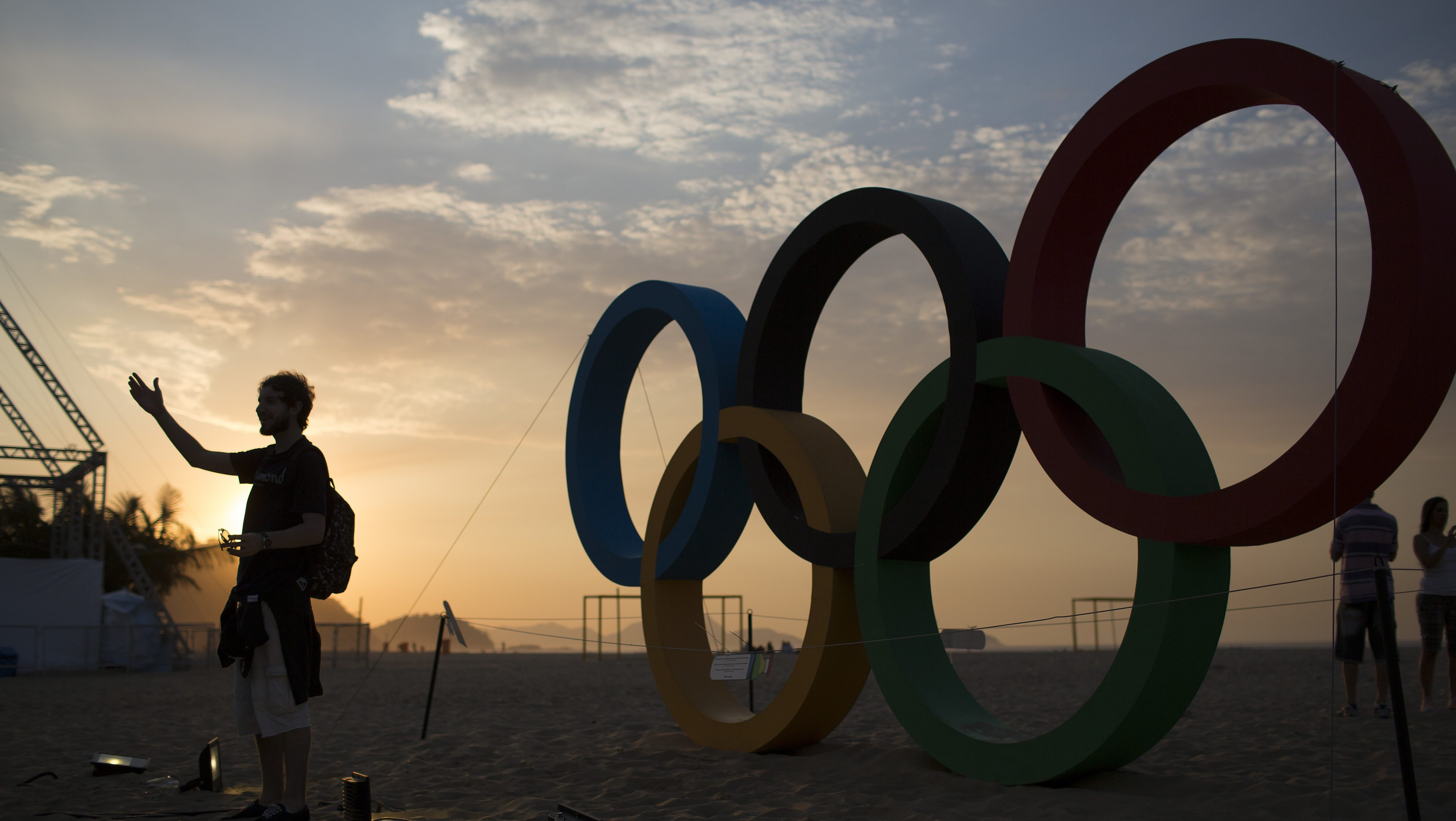 A man poses for a photo in front of the Olympic rings as the sun rises at the Copacabana beach in Rio de Janeiro, Brazil, Saturday, Aug. 20, 2016.
