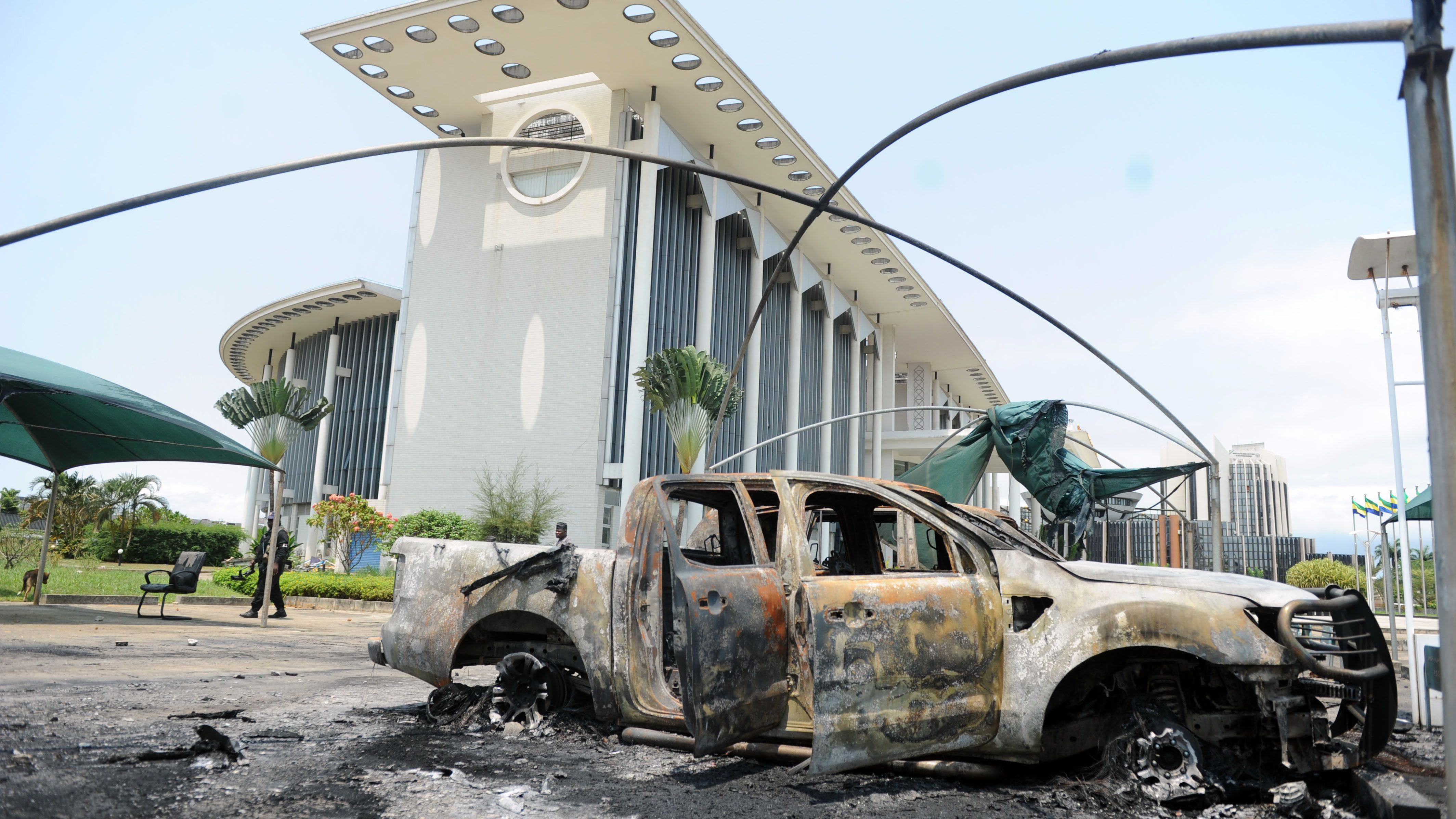 Burnt out cars are seen outside a government building, following an election protest in Libreville, Gabon, Thursday Sept. 1, 2016. Gabon's newly re-elected president sought to assert authority Thursday as the presidential guard attacked the opposition candidate's party headquarters overnight, killing at least one person and injuring more than a dozen amid fiery protests that have seen hundreds detained and the internet blocked.